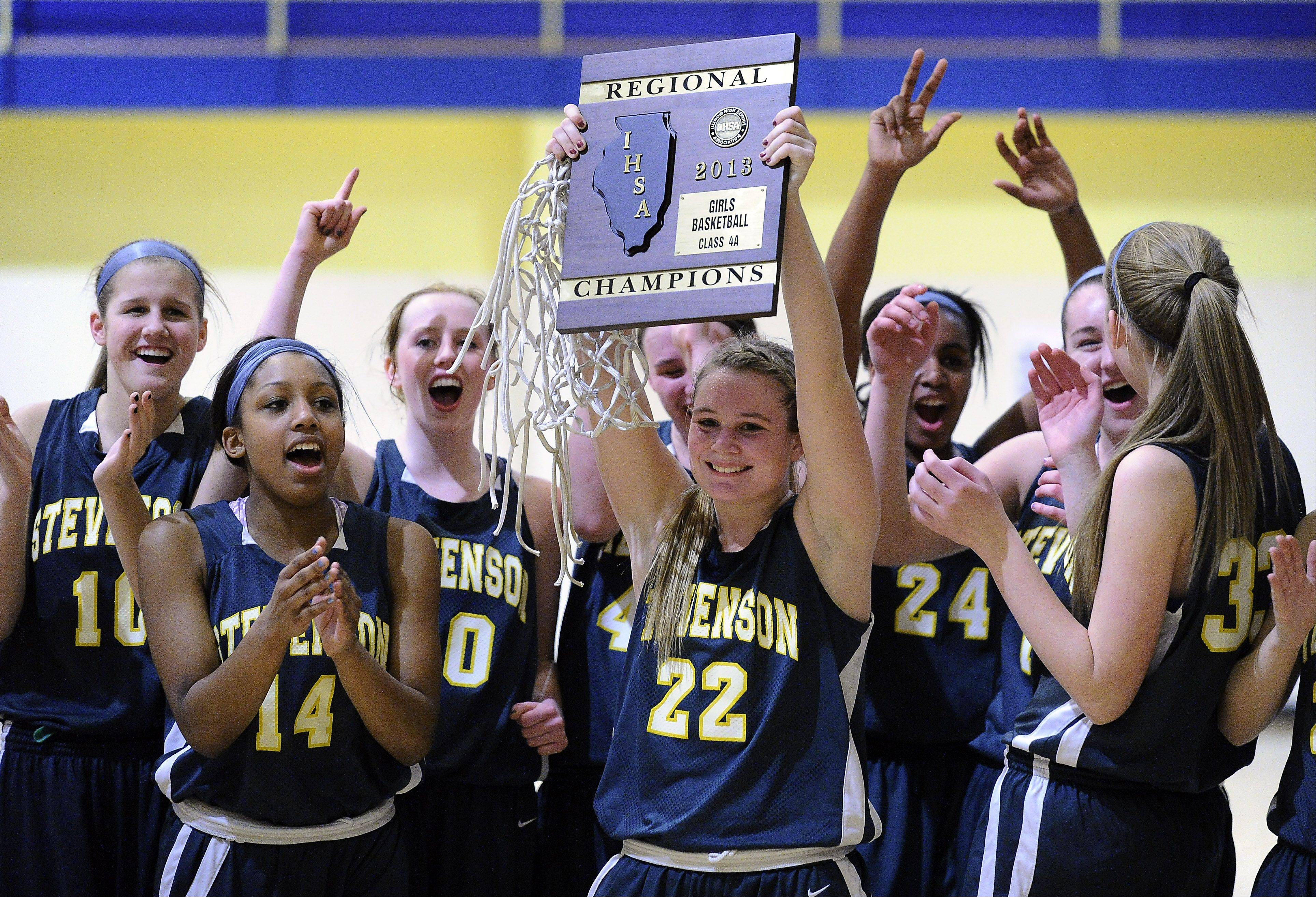 Stevenson's Kari Moffat holds up the regional championship plaque while the rest of her teammates celebrate after the Patriots beat Palatine in the Class 4A regional final at Wheeling on Thursday.