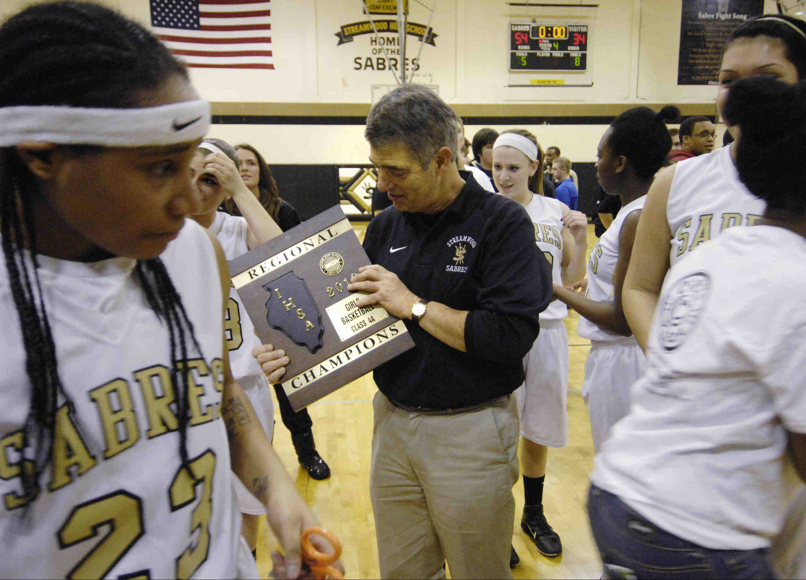 Streamwood girls basketball coach George Rosner admires the regional championship plaque his team won Thursday night, beating South Elgin 54-34 in the Class 4A final at Streamwood. It's the Sabres' first regional crown since 1988, a team which was also coached by Rosner.