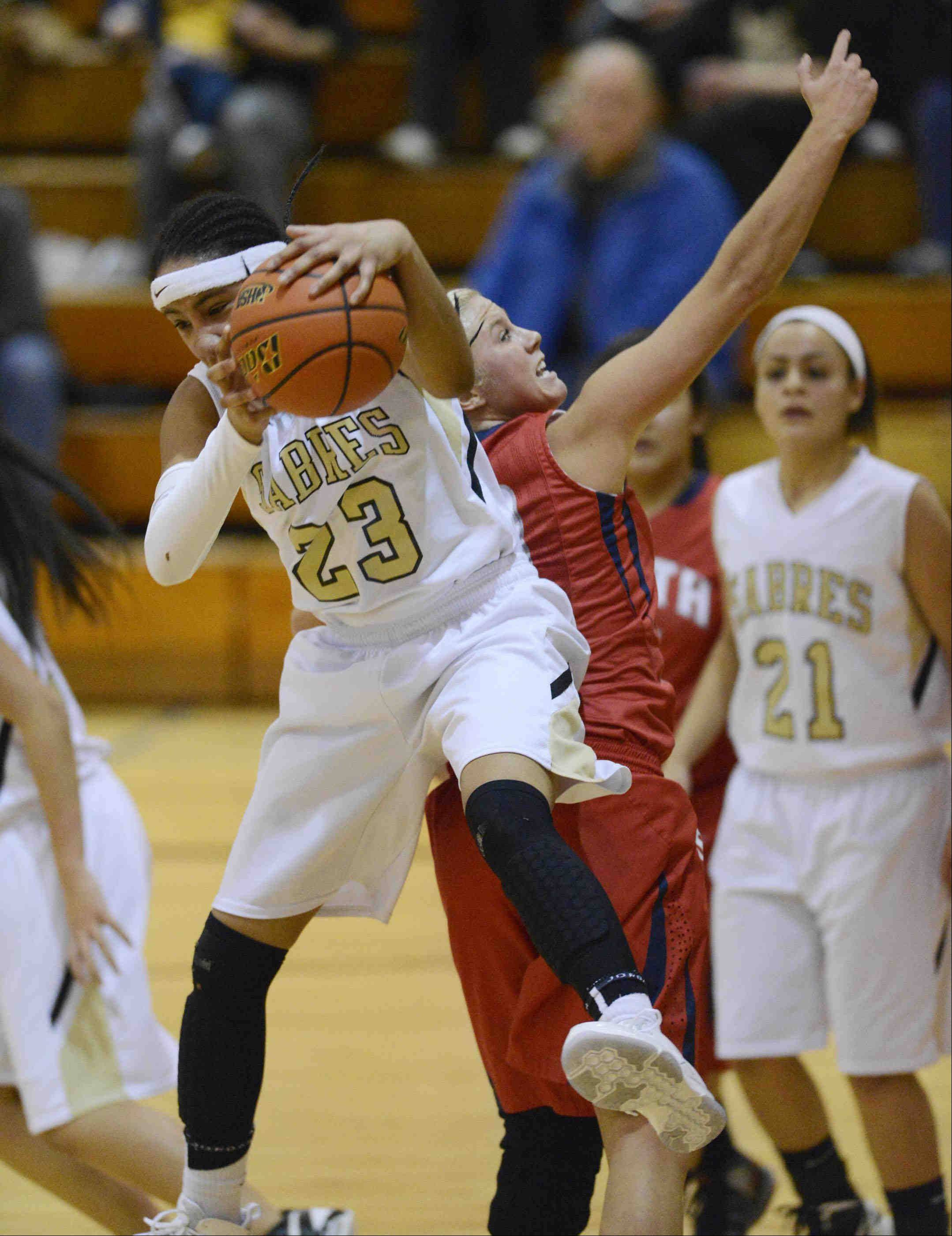 Streamwood's Deja Moore takes a rebound away from South Elgin's Kara Rodriguez.