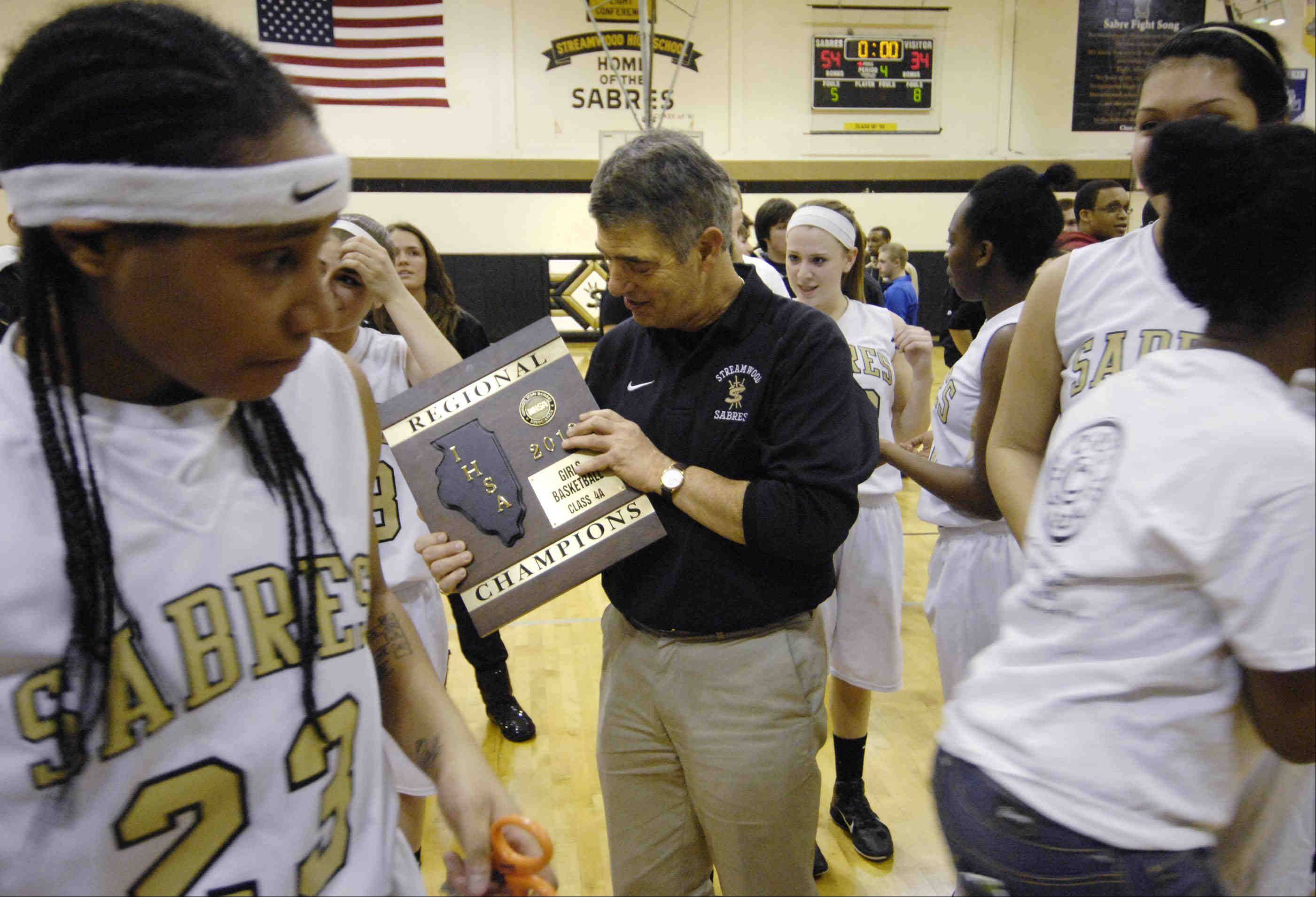 Streamwood head coach George Rosner looks at the regional championship plaque after defeating South Elgin.