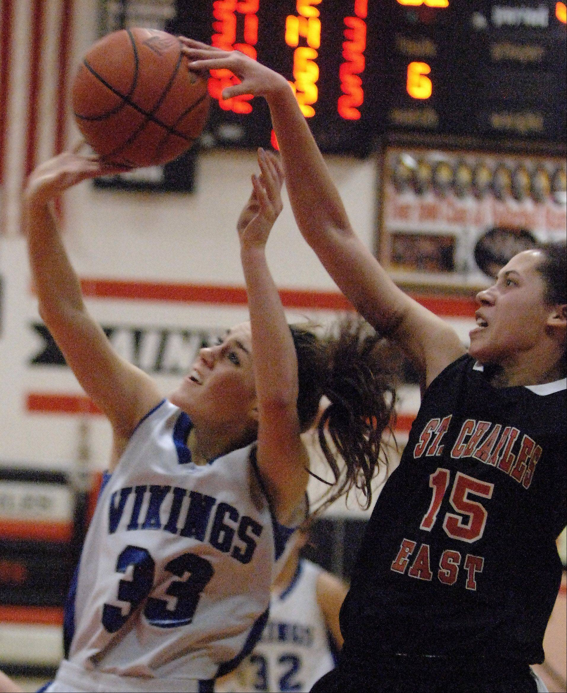 St. Charles East's Kyra Washington is called for a foul against Geneva's Madeline Dunn.