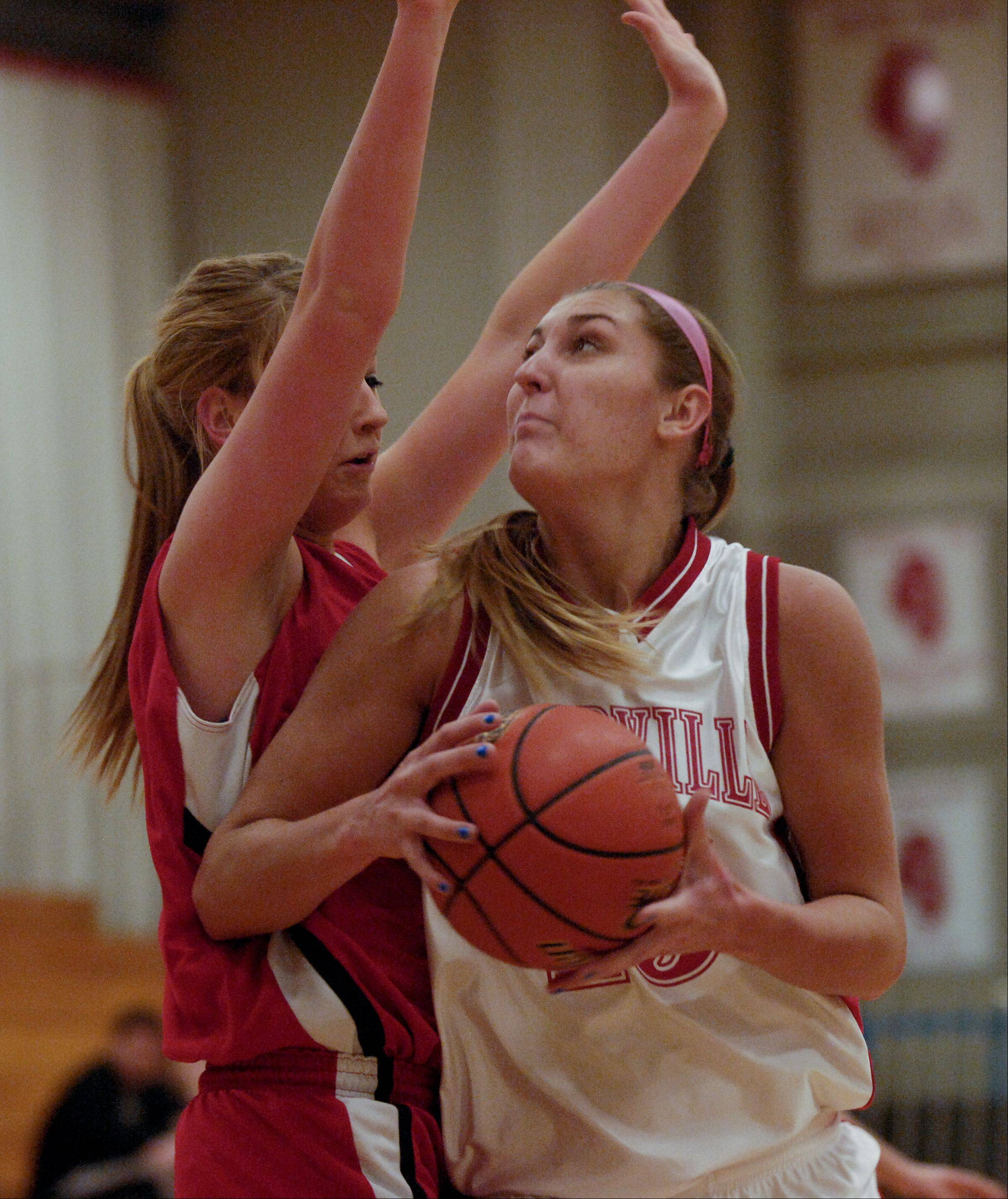 Victoria Trowbridge of Naperville Central heads to the hoop past Emily Schramek of Benet Academy .