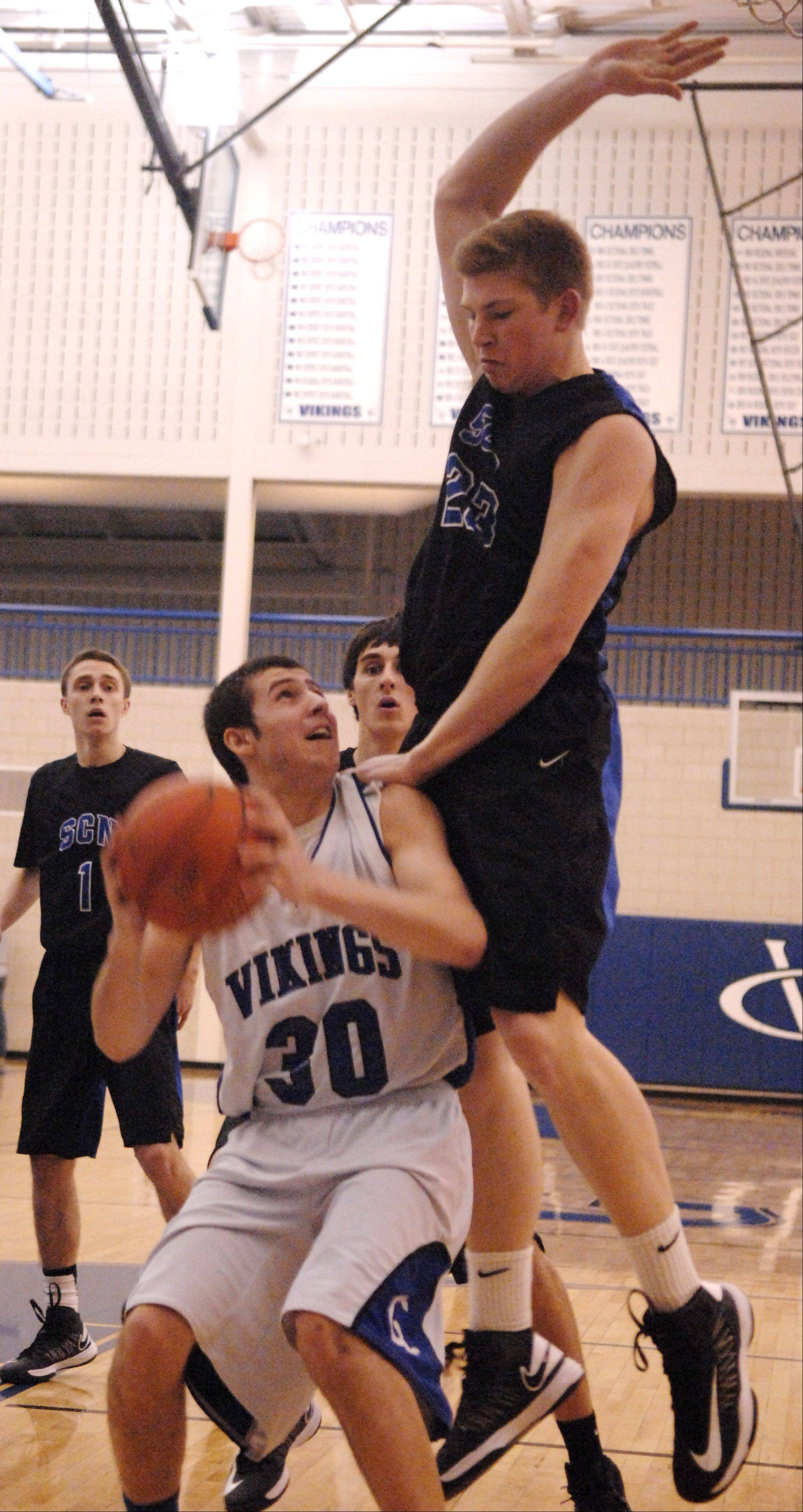 Geneva's Chris Parrilli draws a fouled by St. Charles North's Justin Stanko with a pump fake during Friday's game in Geneva.