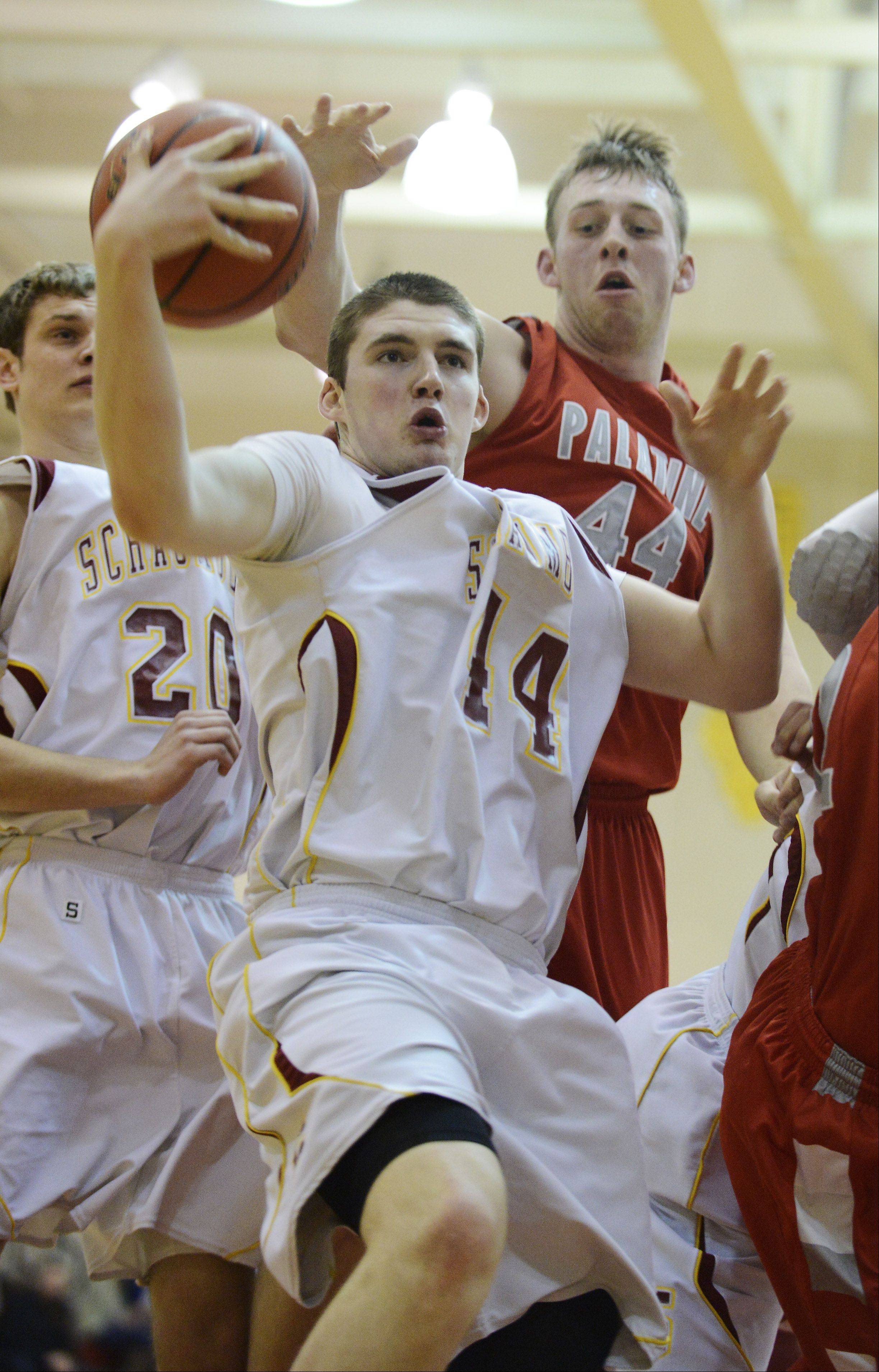 Schaumburg's Jimmy Lundquist grabs a rebound as Palatine's Baldus tries to knock the ball loose during Friday's MSL West game at Schaumburg.