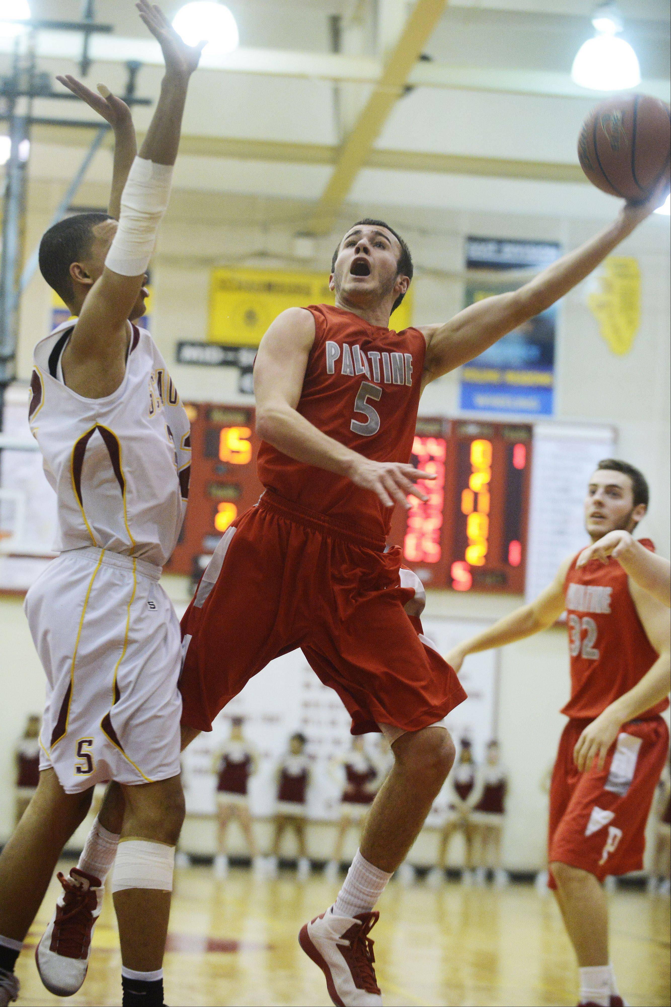 Palatine's Chris Macahon takes a layup against the defense of Schaumburg's Brandan Parker on Friday.