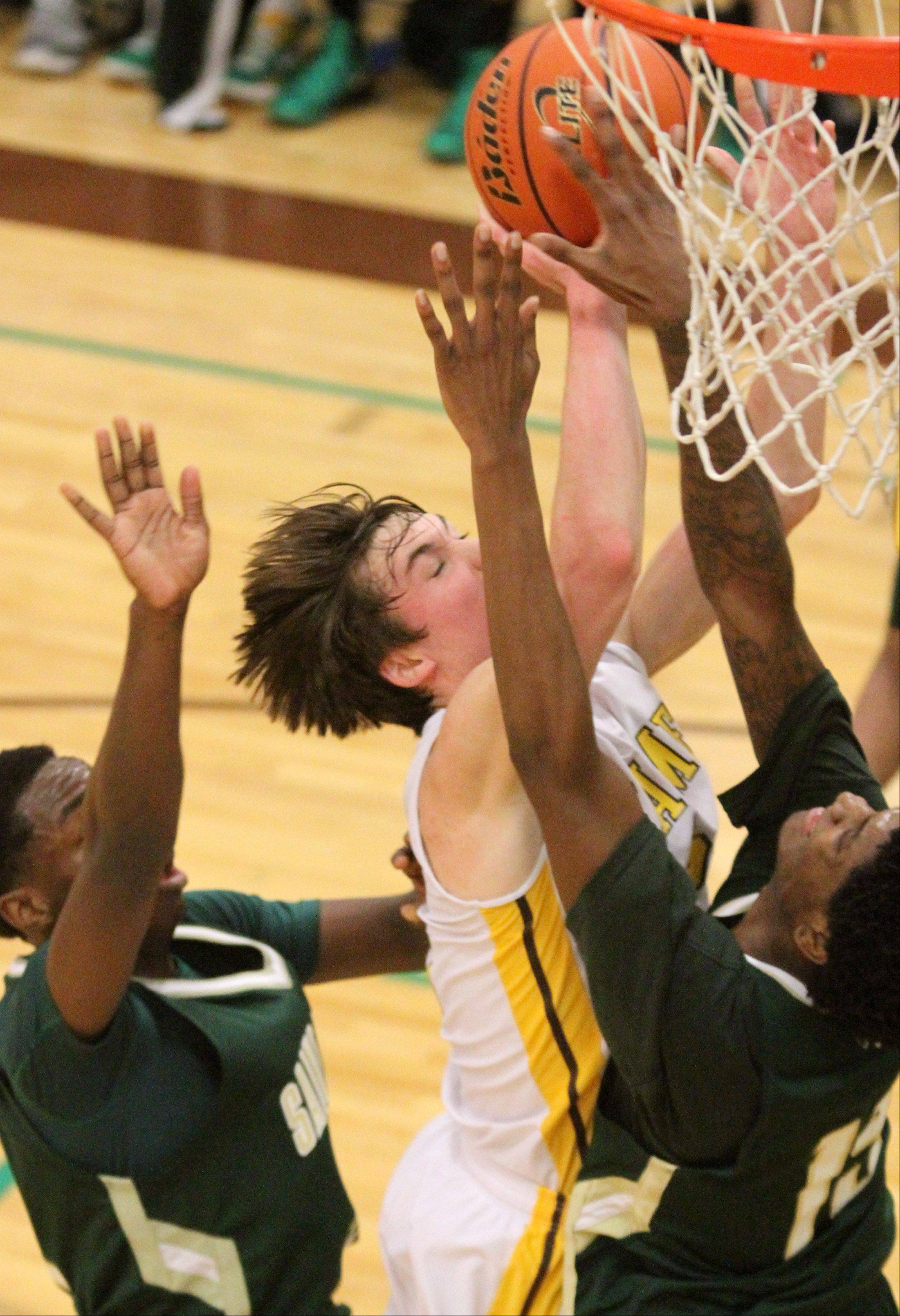 Carmel's Greg Edkins shoots over St. Patrick defenders Isaac Moore, left, and Keith Langston at Carmel on Friday.