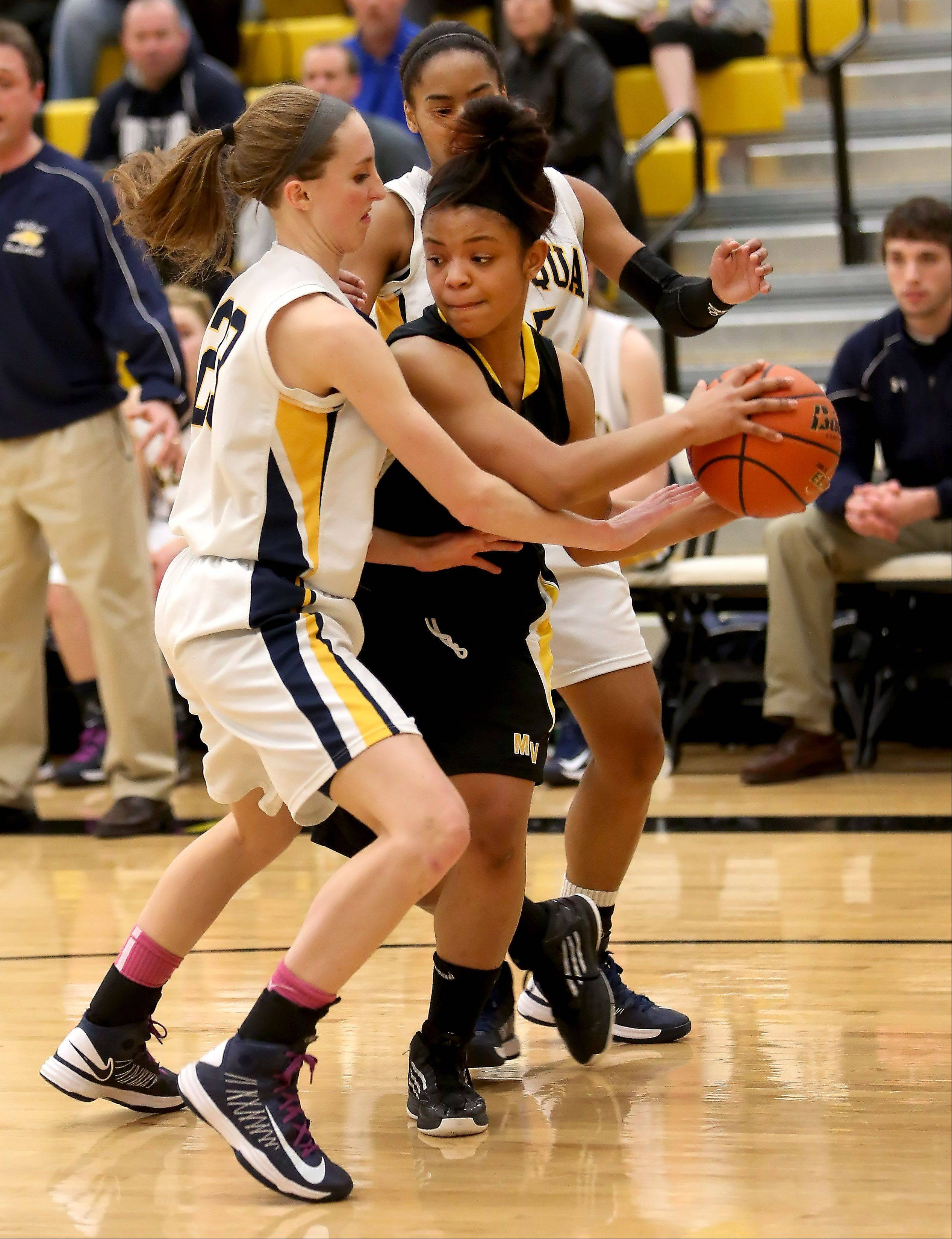 Kellee Clay of Metea Valley, right, looks for room to pass around Allison Hedrick of Neuqua Valley during girls basketball Class 4A regional final on Friday in Aurora.