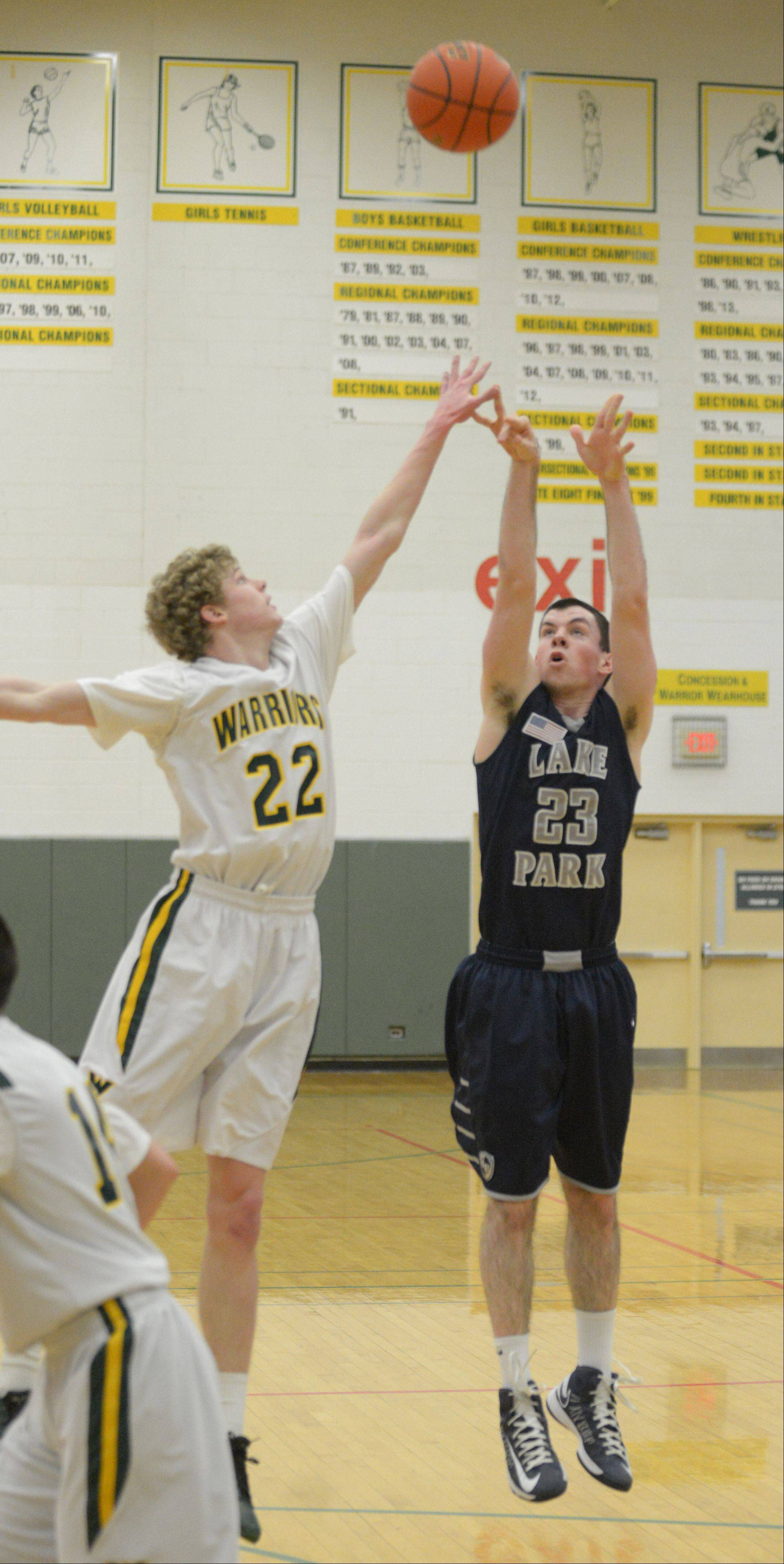 Jack Cordes of Waubonsie, left, attempts to block a shot by Sean Moore of Lake Park during the Lake Park at Waubonsie Valley boys basketball game Friday.