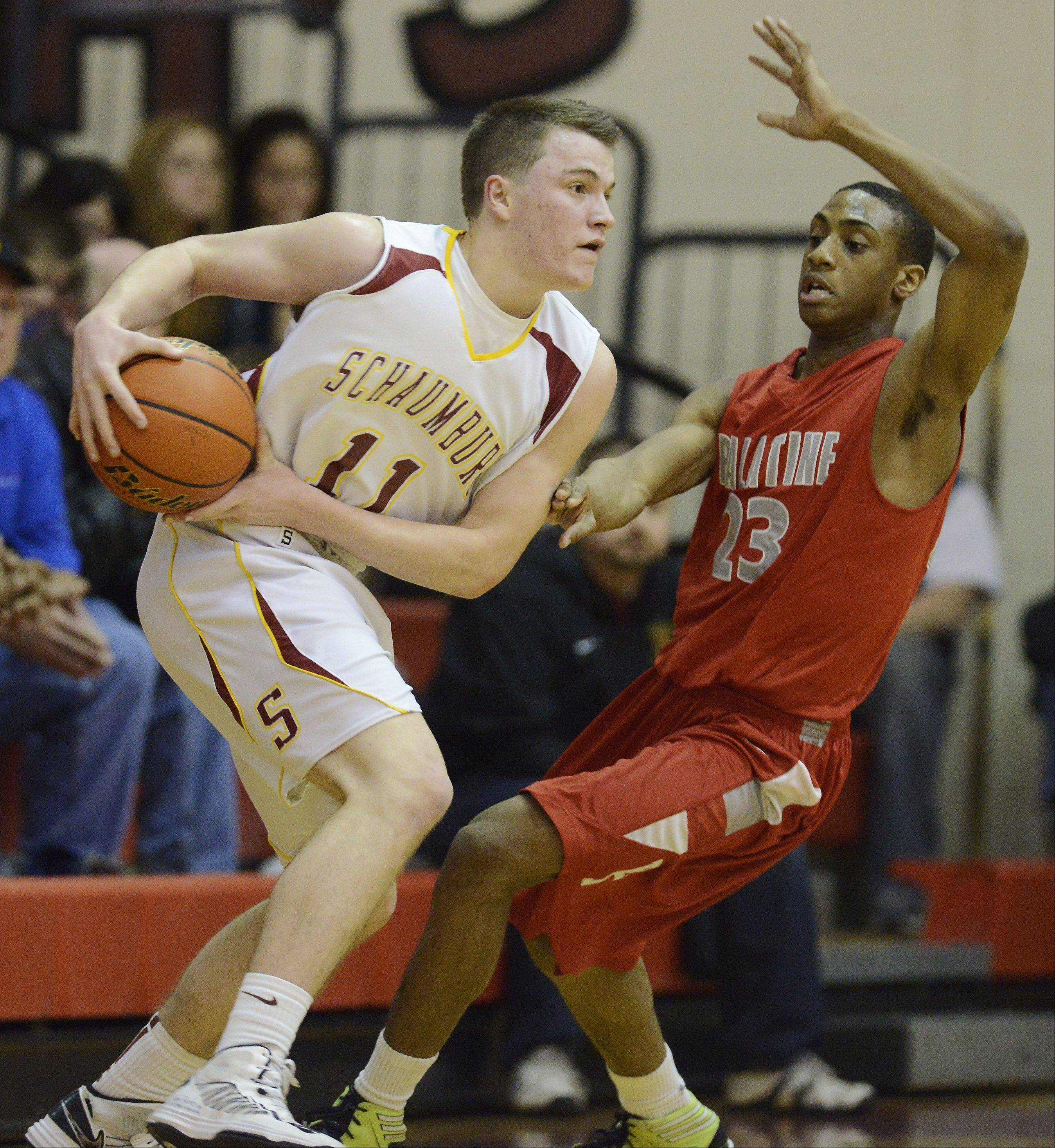 Schaumburg's Cole Reyes looks for an open teammate while being closely guarded by Palatine's Roosevelt Smart.