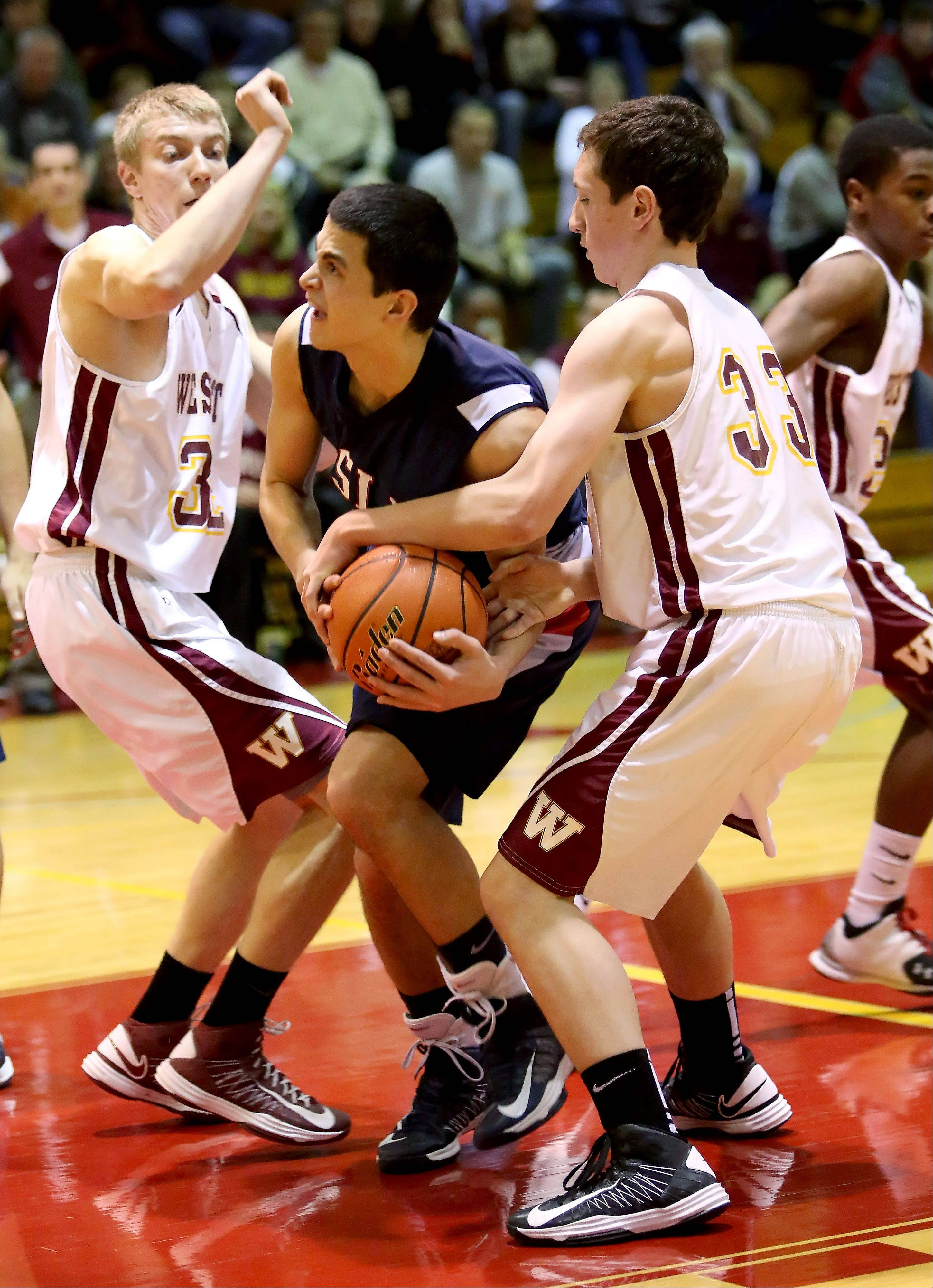 Jerremy Glavanovits of Lisle gets sandwiched in between Jean Pietrzak, left and John Kelly, right, of Westmont in Class 2A regional boys basketball on Monday in Westmont.