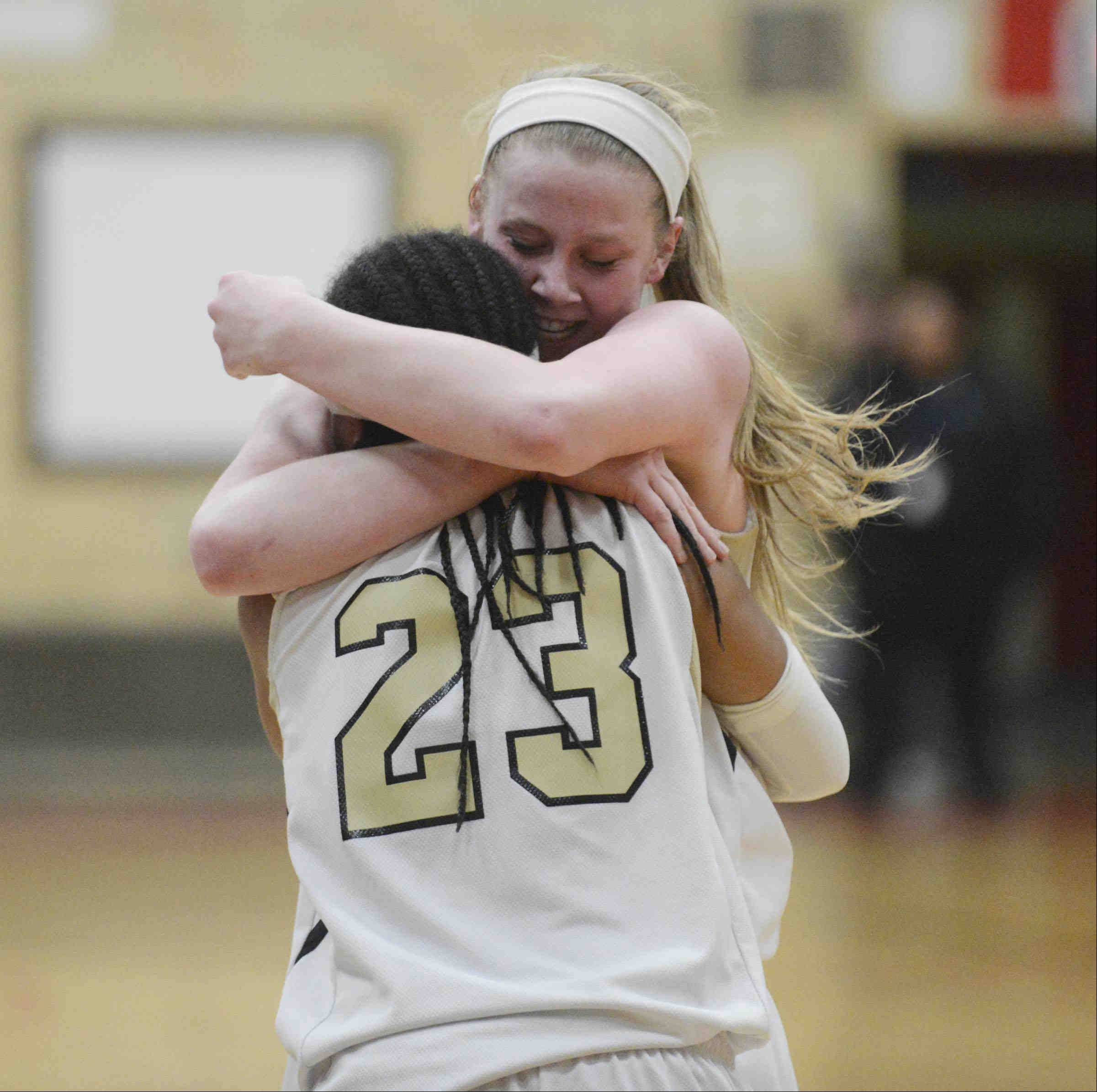 Streamwood's Hannah McGlone and Deja Moore (23) hug after the Sabres defeated Cary-Grove Monday in the Class 4A sectional game in Rockford.