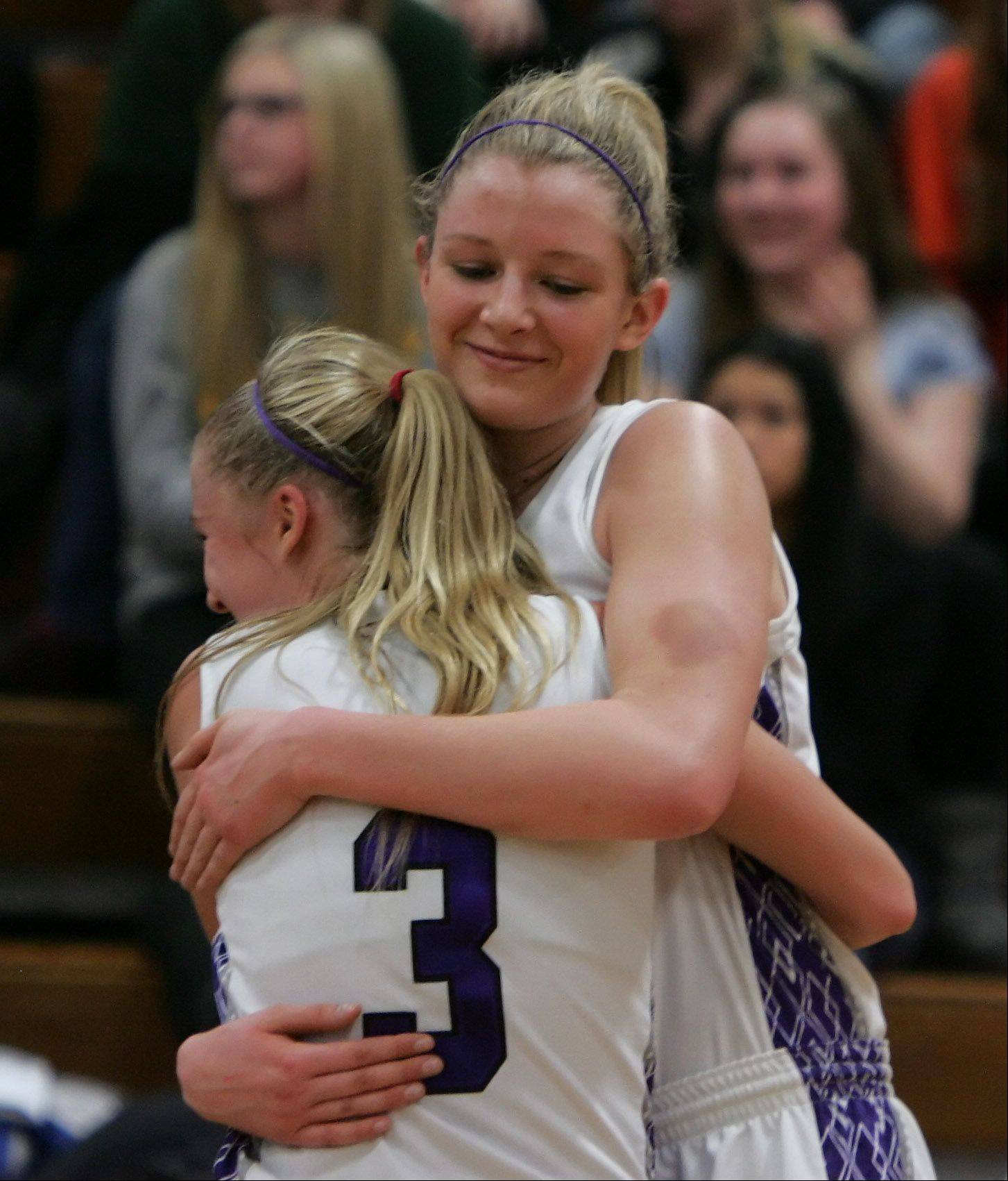 Rolling Meadows players Jackie Kemph, left, and Jenny Vliet hug after winning the game against Stevenson during the girls basketball game between Rolling Meadows and Stevenson in the Class 4A sectional semifinals at Libertyville High School Monday.