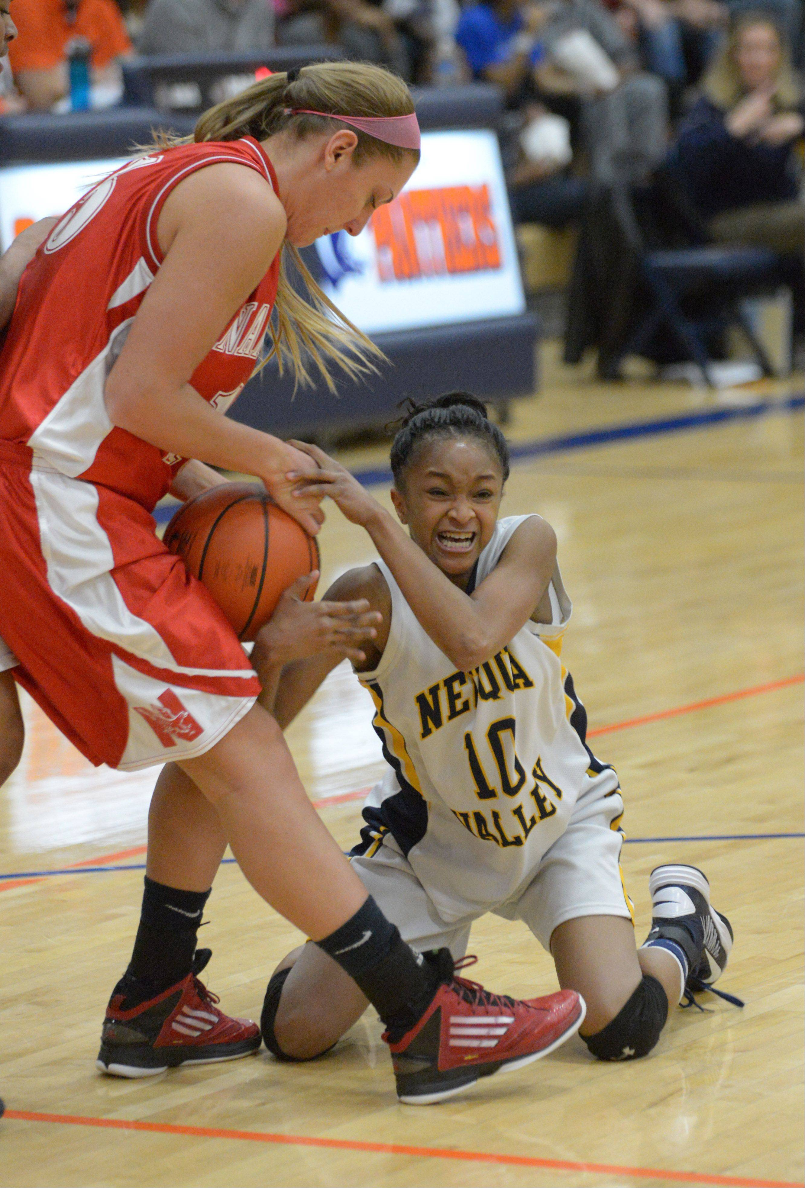 Laura Dierking,left, of Naperville Central and Myia Starks of Neuqua fight for a loose ball during the Neuqua Valley vs Naperville Central game in Oswego Tuesday. This was semifinal action.