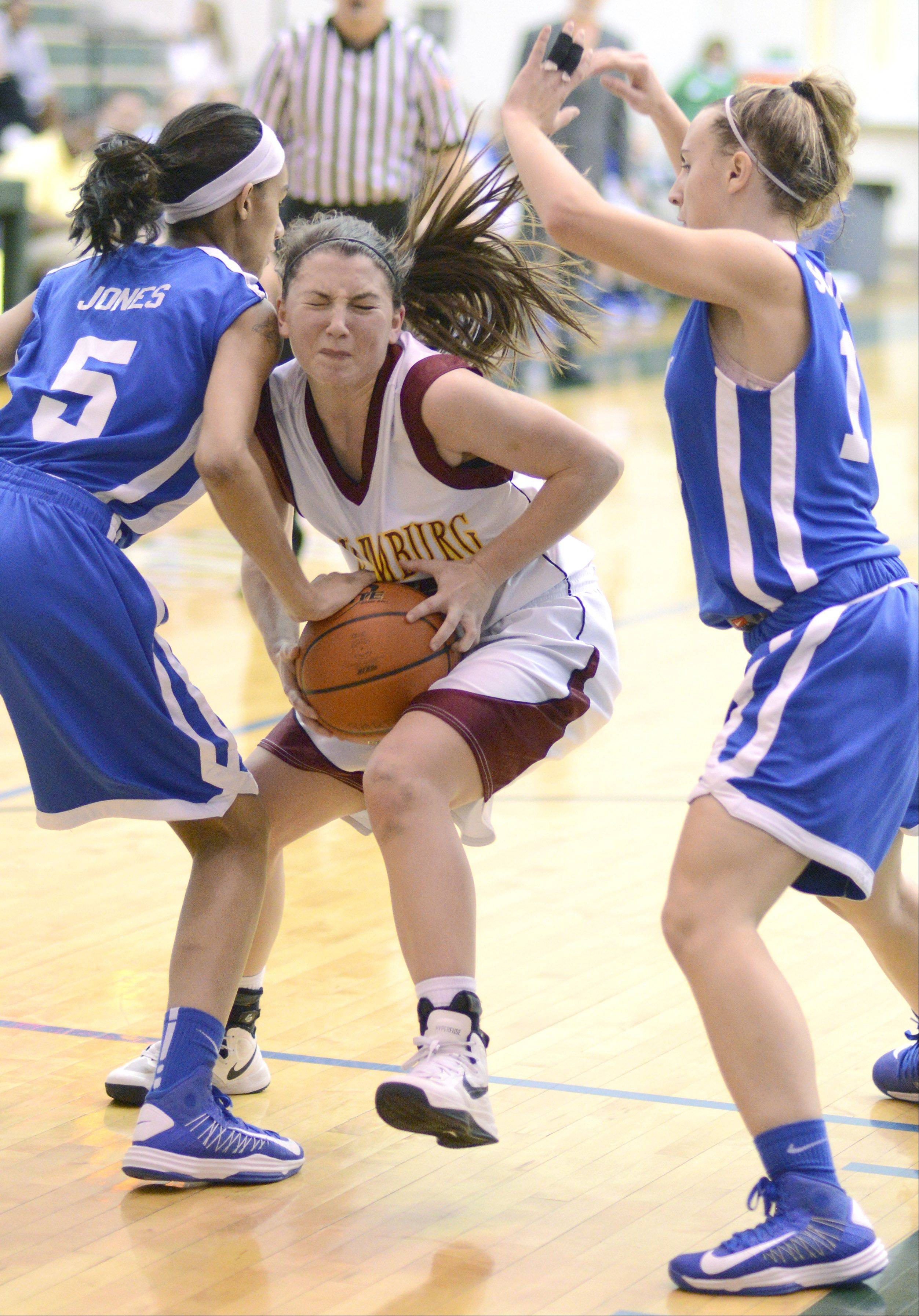 Schaumburg's Amanda Kelly fights through a block by Wheaton North in the second quarter of the Class 4A regional game on Tuesday, February 19.
