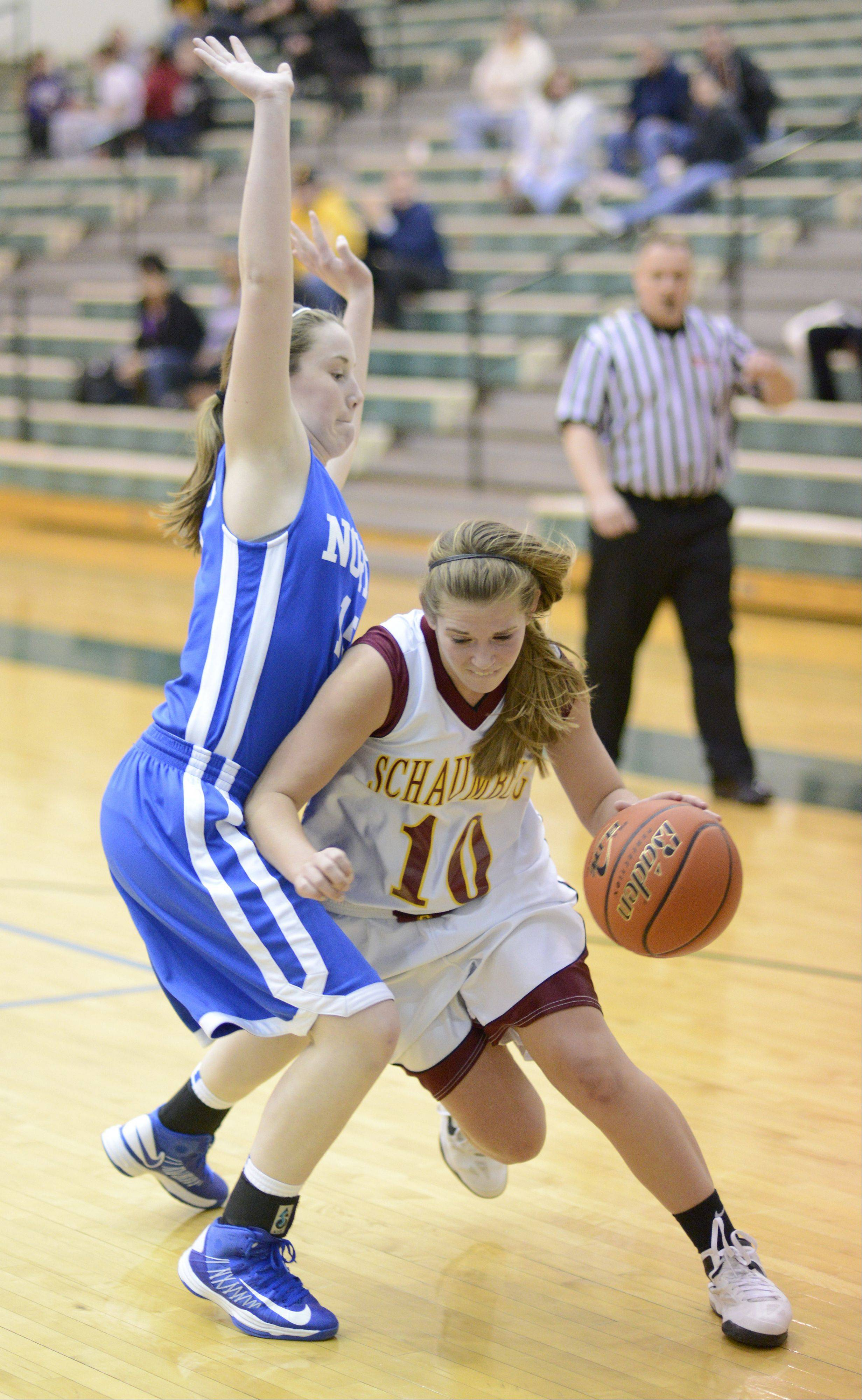 Schaumburg's Riley Williams maneuvers around a block by Wheaton North's Kelly Thornton in the third quarter of the Class 4A regional game on Tuesday, February 19.