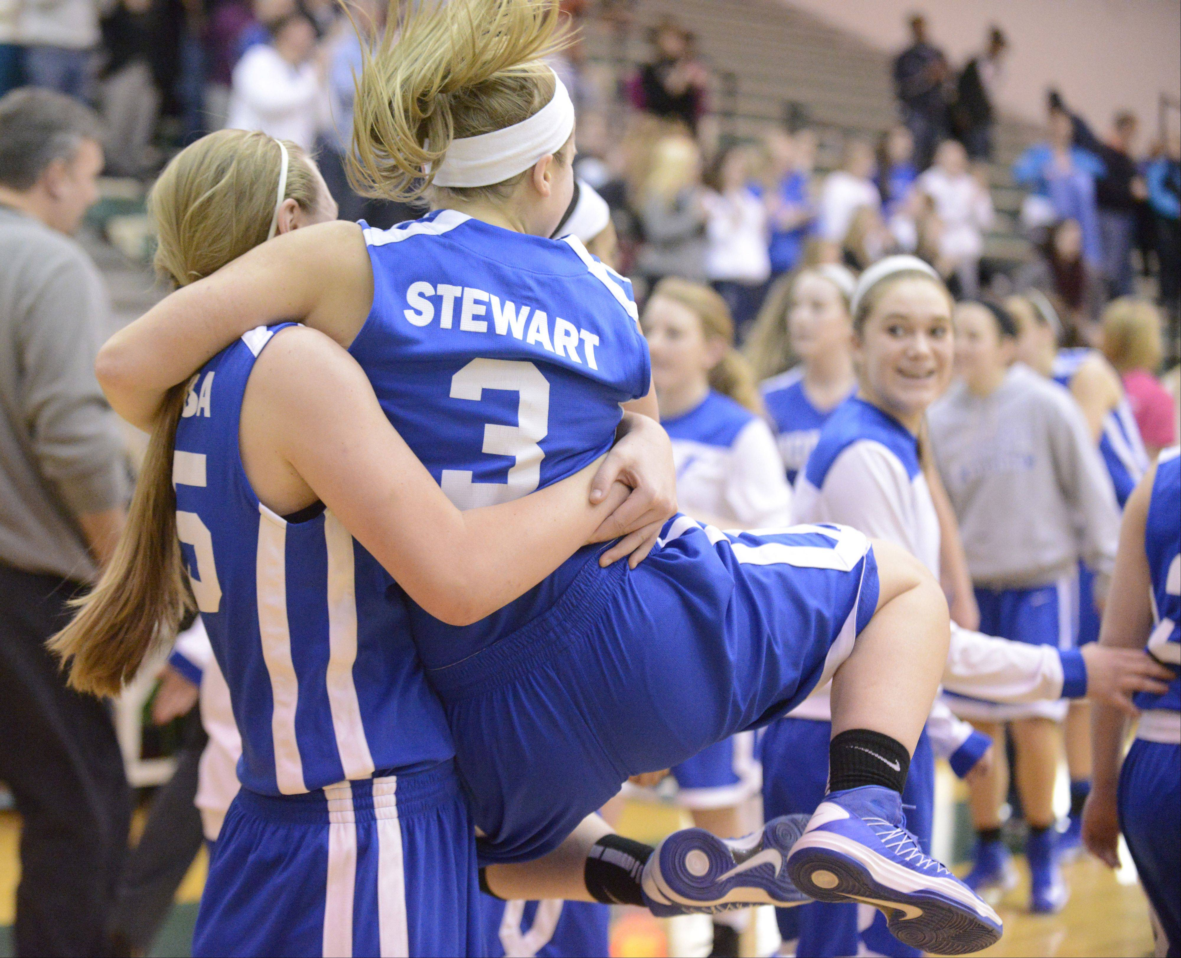 Wheaton North's Mandy Traversa lifts teammate Reilly Stewart as she clicks her heels after their win over Schaumburg in the Class 4A regional game on Tuesday, February 19.