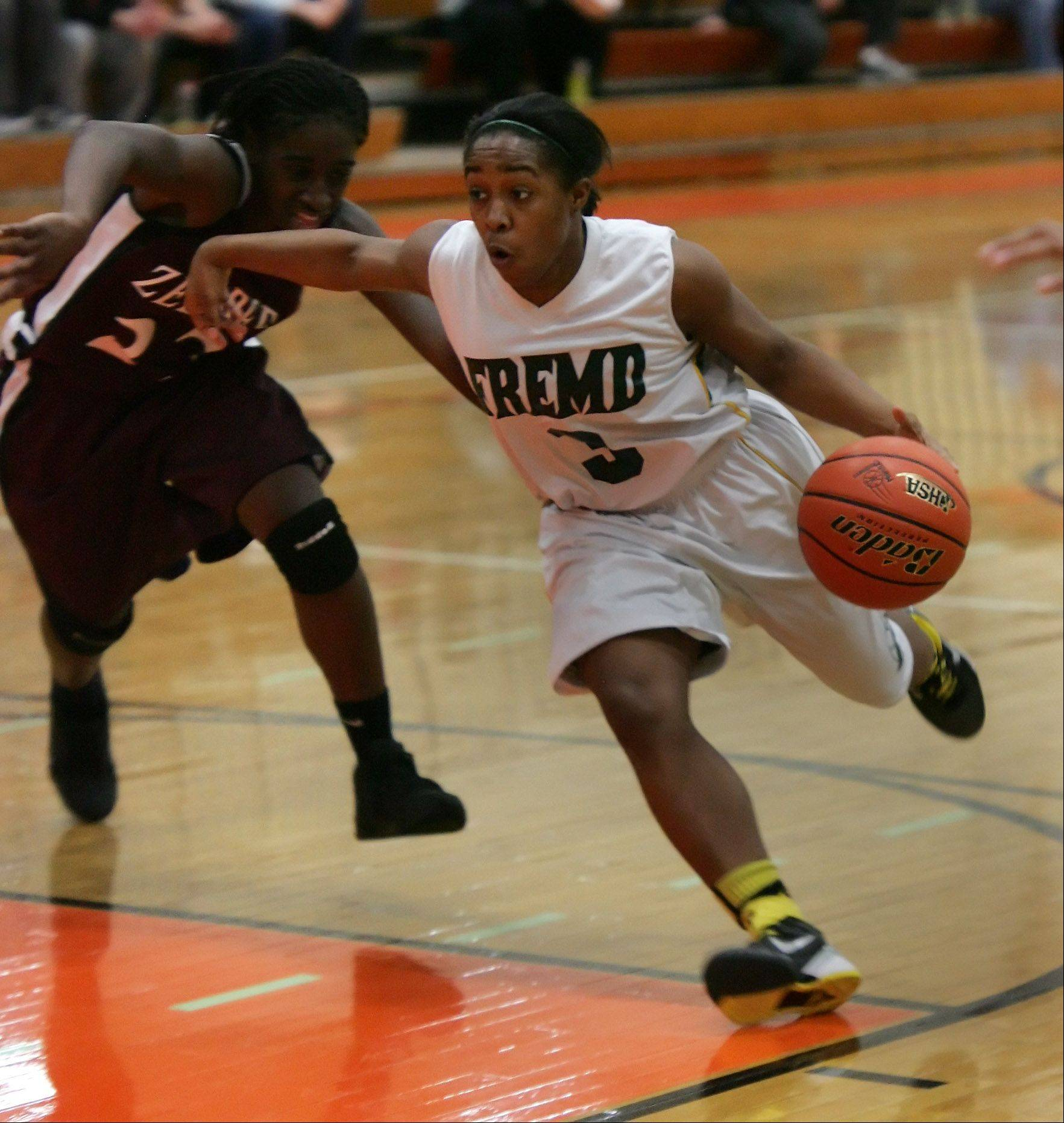 Fremd guard Brianna Lewis drives around Zion-Benton player T.T. Maggett during Class 4A sectional semifinal play at Libertyville High School on Monday.