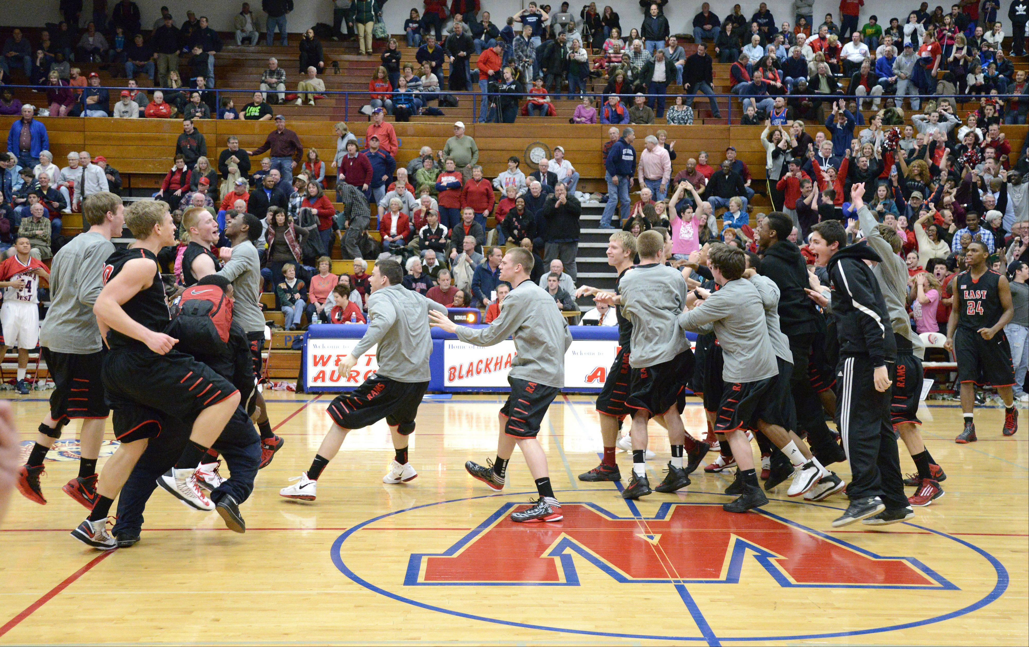 Glenbard East teammates storm the floor after their win over West Aurora in double over time on Wednesday, February 20.