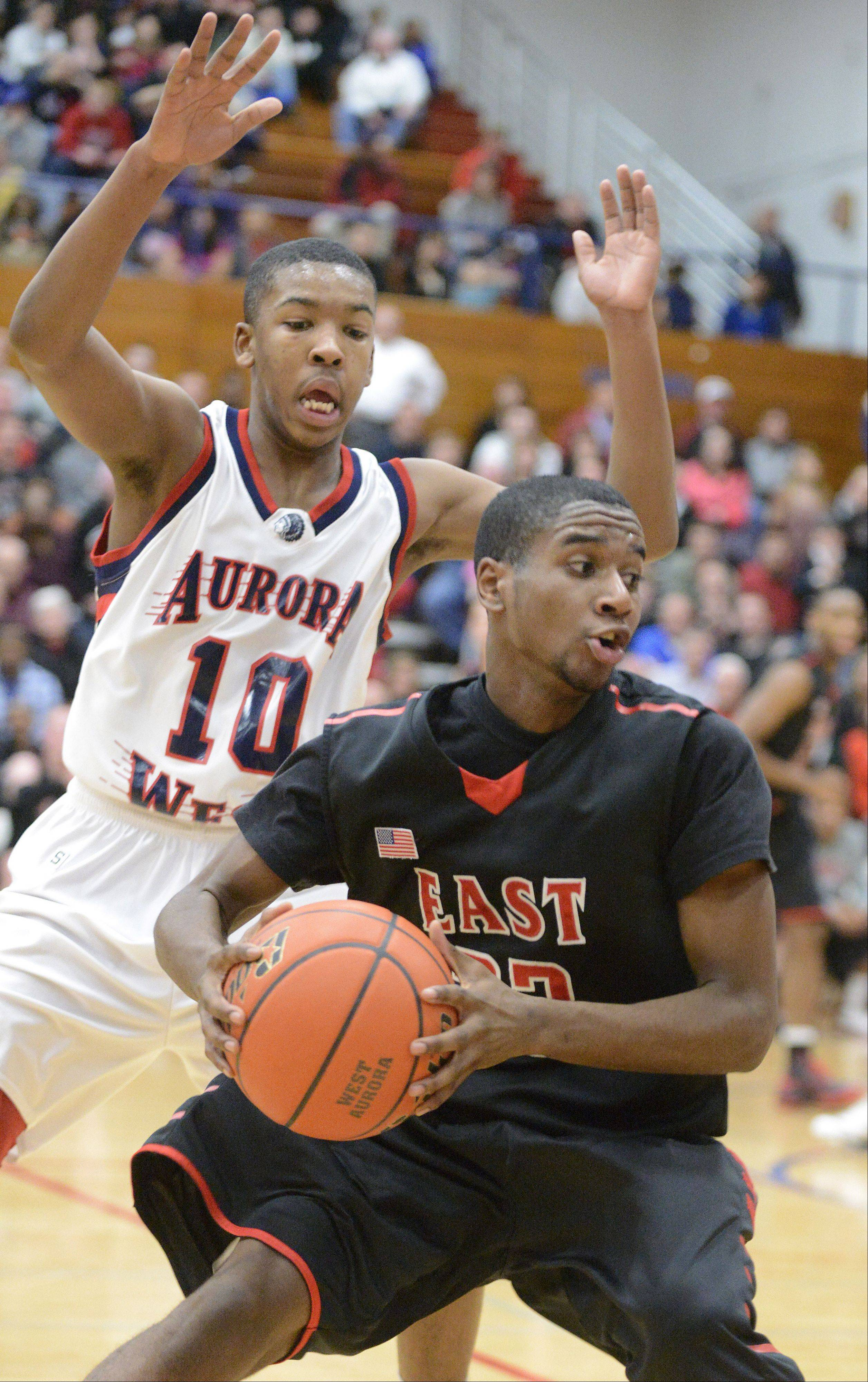 Glenbard East's Jason Hill spins to avoid a block by West Aurora's Jontrell Walker in the second over time period on Wednesday, February 20. 2