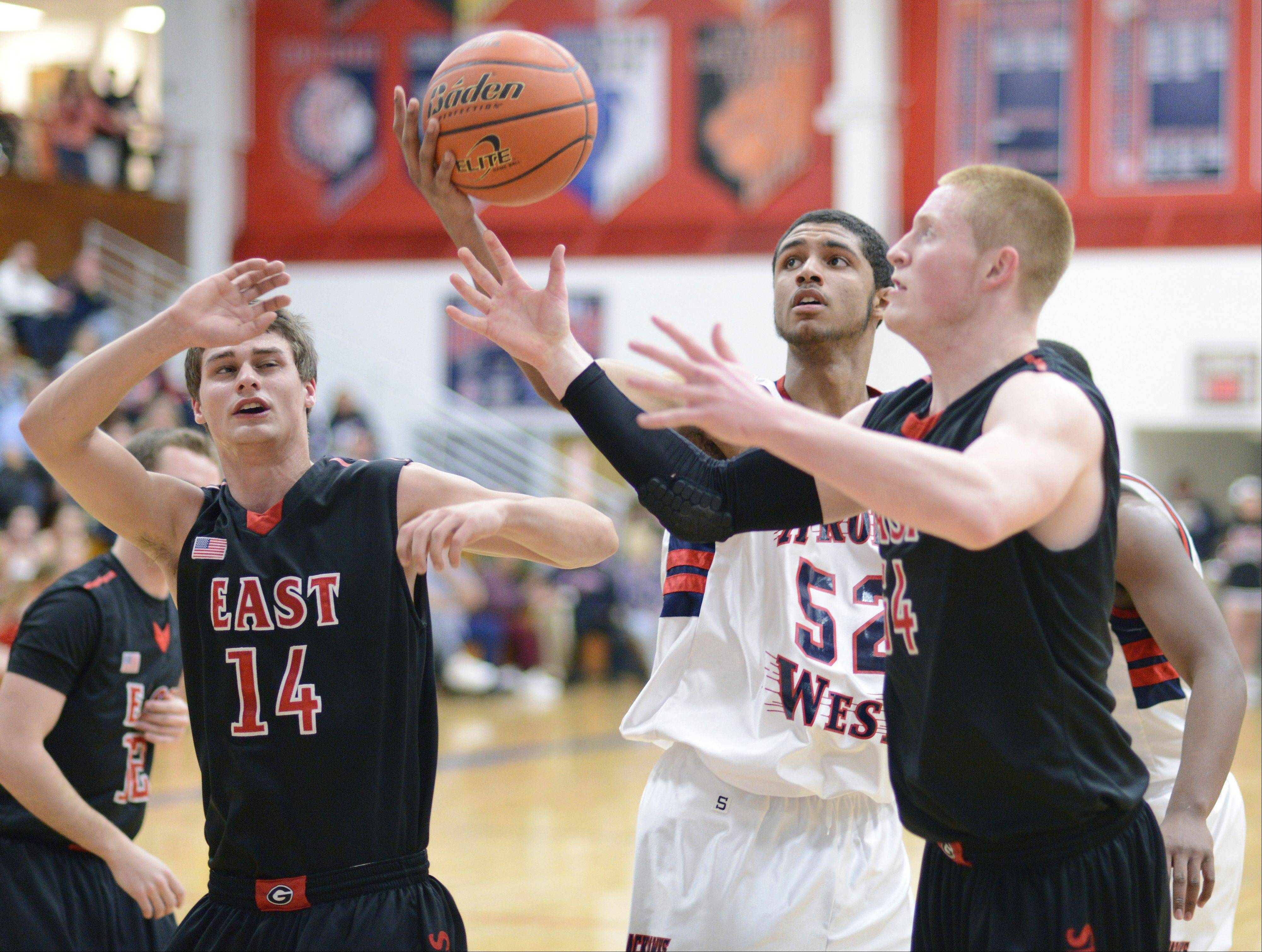 Glenbard East's Mike Kjeldsen and Brandon Havenga scramble for a rebound with West Aurora's Joshua McAuley in the fourth quarter on Wednesday, February 20.