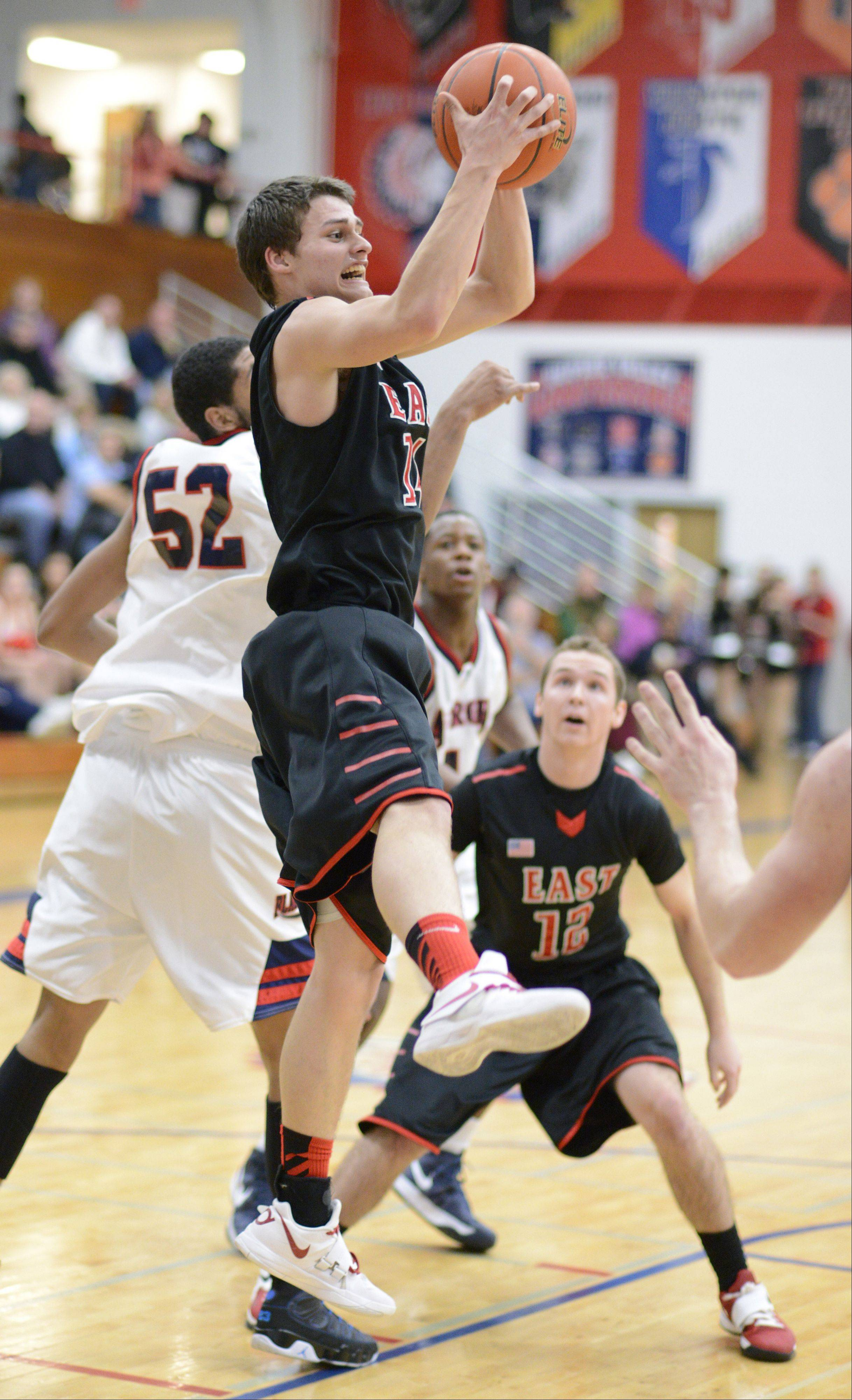 Glenbard East's Mike Kjeldsen snatches a rebound in front of West Aurora's Joshua McAuley in the third quarter on Wednesday, February 20.