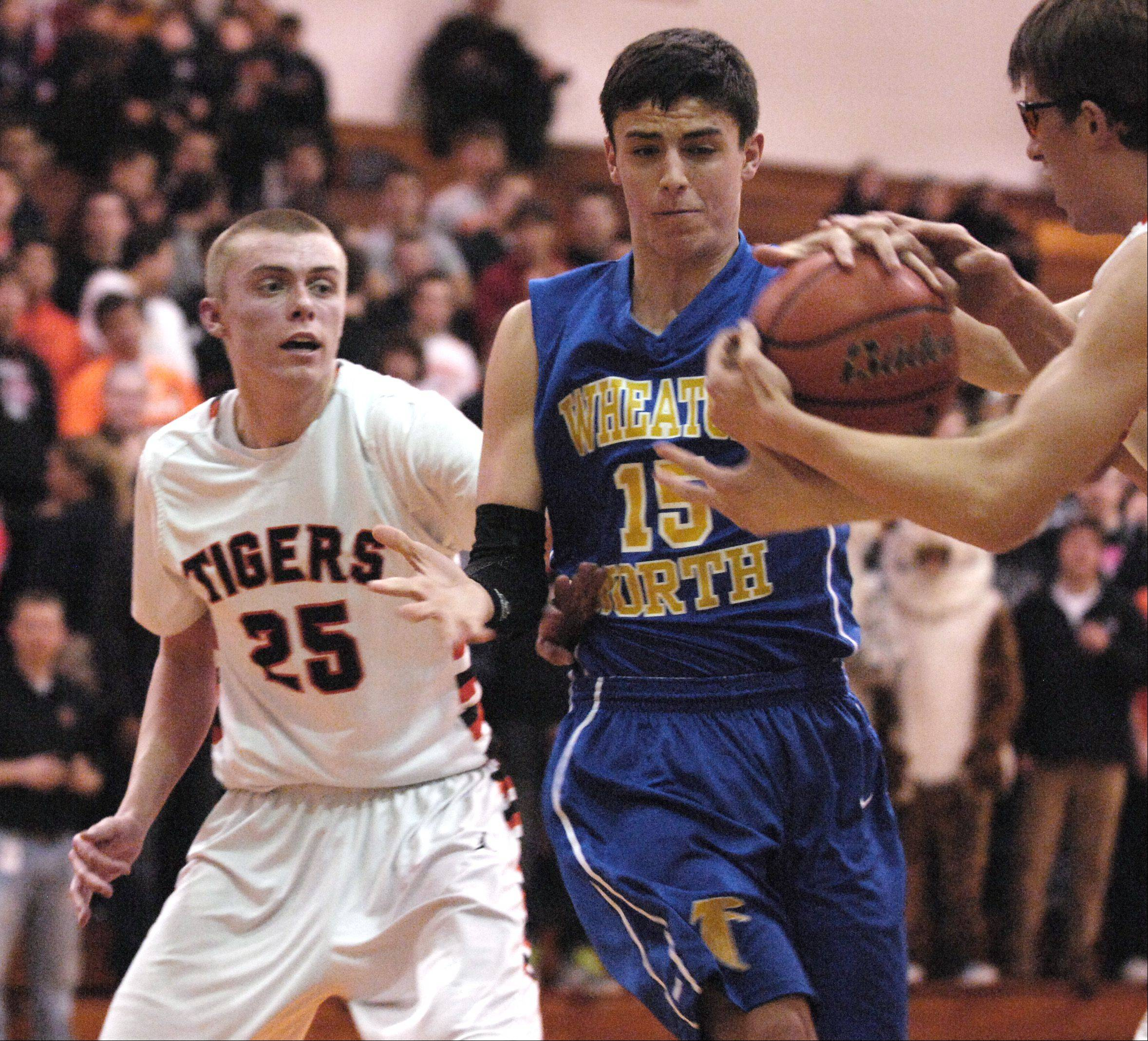Michael Kramer of Wheaton Warrenville South and Mitch Vosberg of Wheaton North battle for control of the ball during boys basketball, Wednesday.