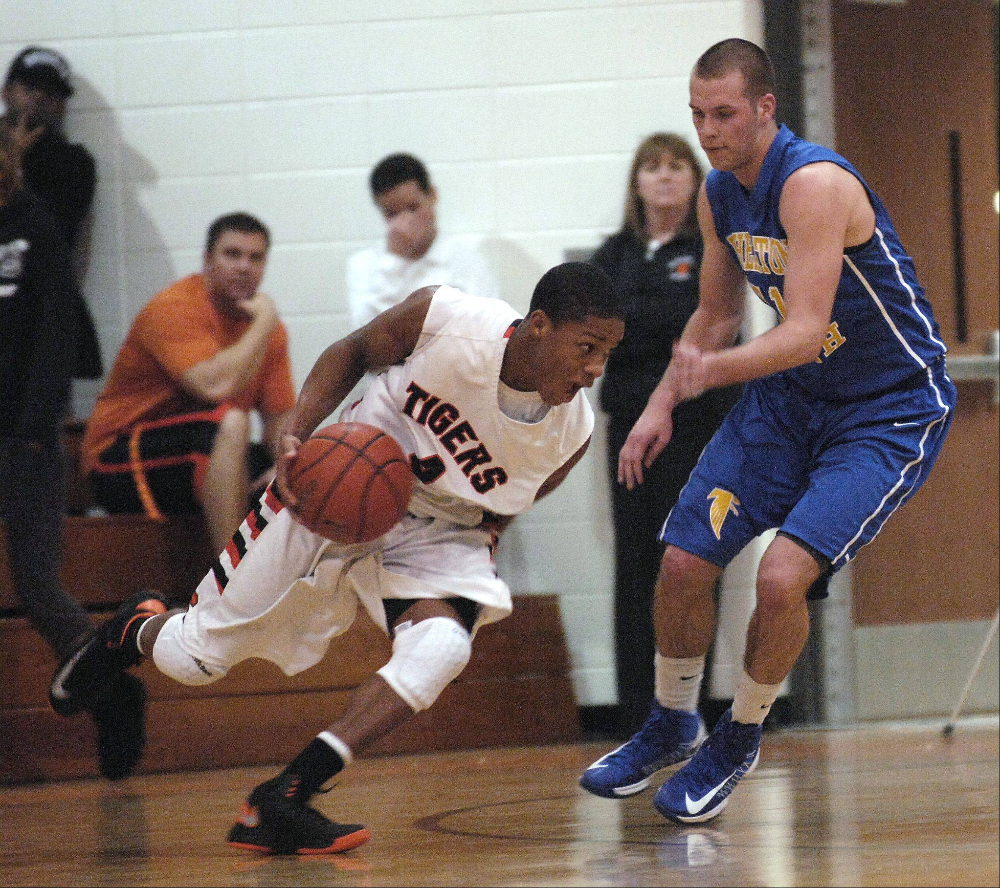 Keishawn Watson of Wheaton Warrenville South drives around Matt Biegalski of Wheaton North during boys basketball, Wednesday.