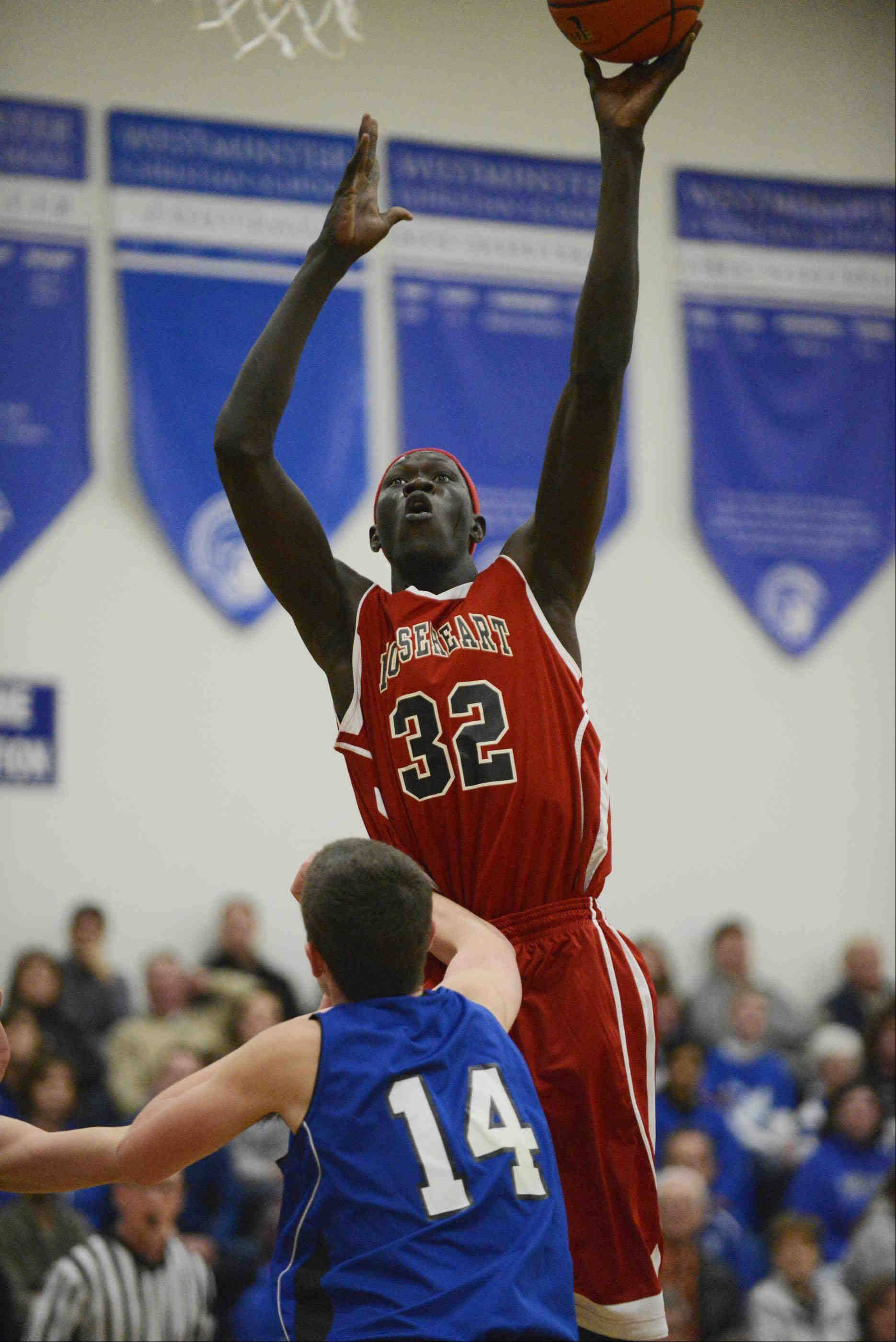 Mooseheart's 6-foot-10 Makur Puou stretches for an easy shot over Westminster Christian's Sam Carani Wednesday in Elgin.