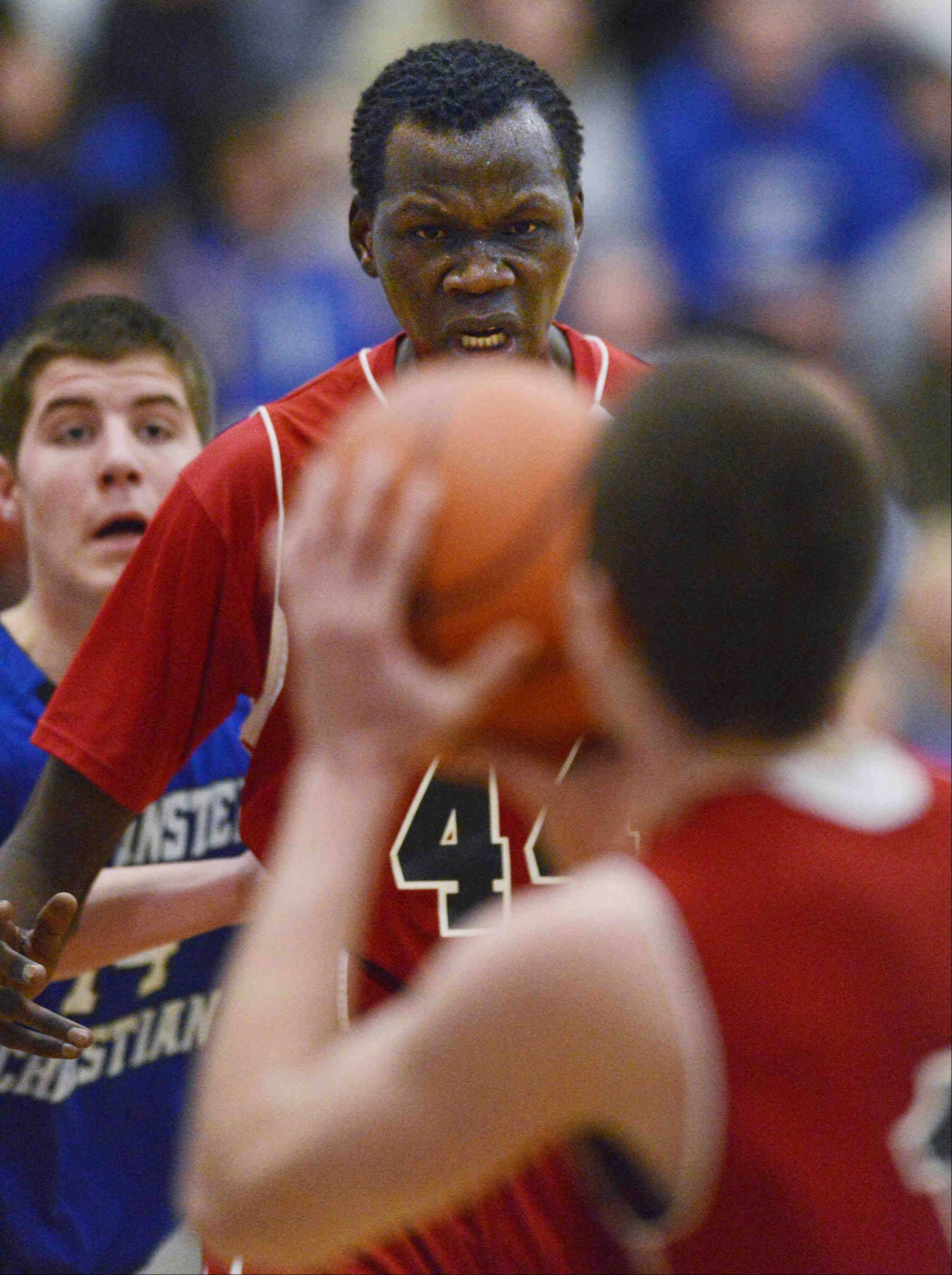 Mooseheart's Akim Nyang tells teammate Peter Kurowski to shoot the ball Wednesday against Westminster Christian in Elgin.