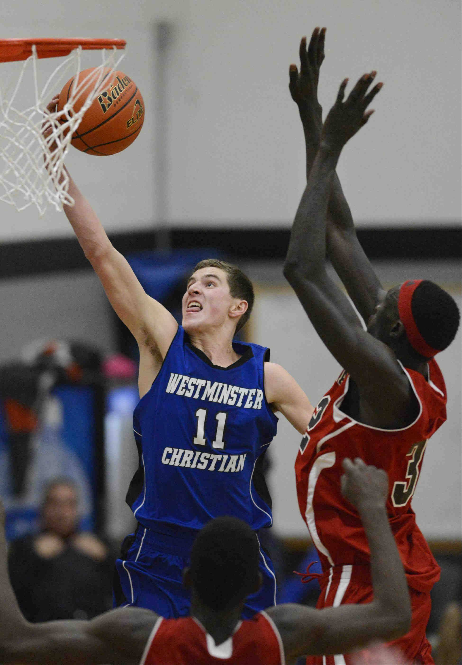 Westminster Christian's Will Woodhouse dries for a layup that is blocked by Mooseheart's Makur Puou Wednesday in Elgin.