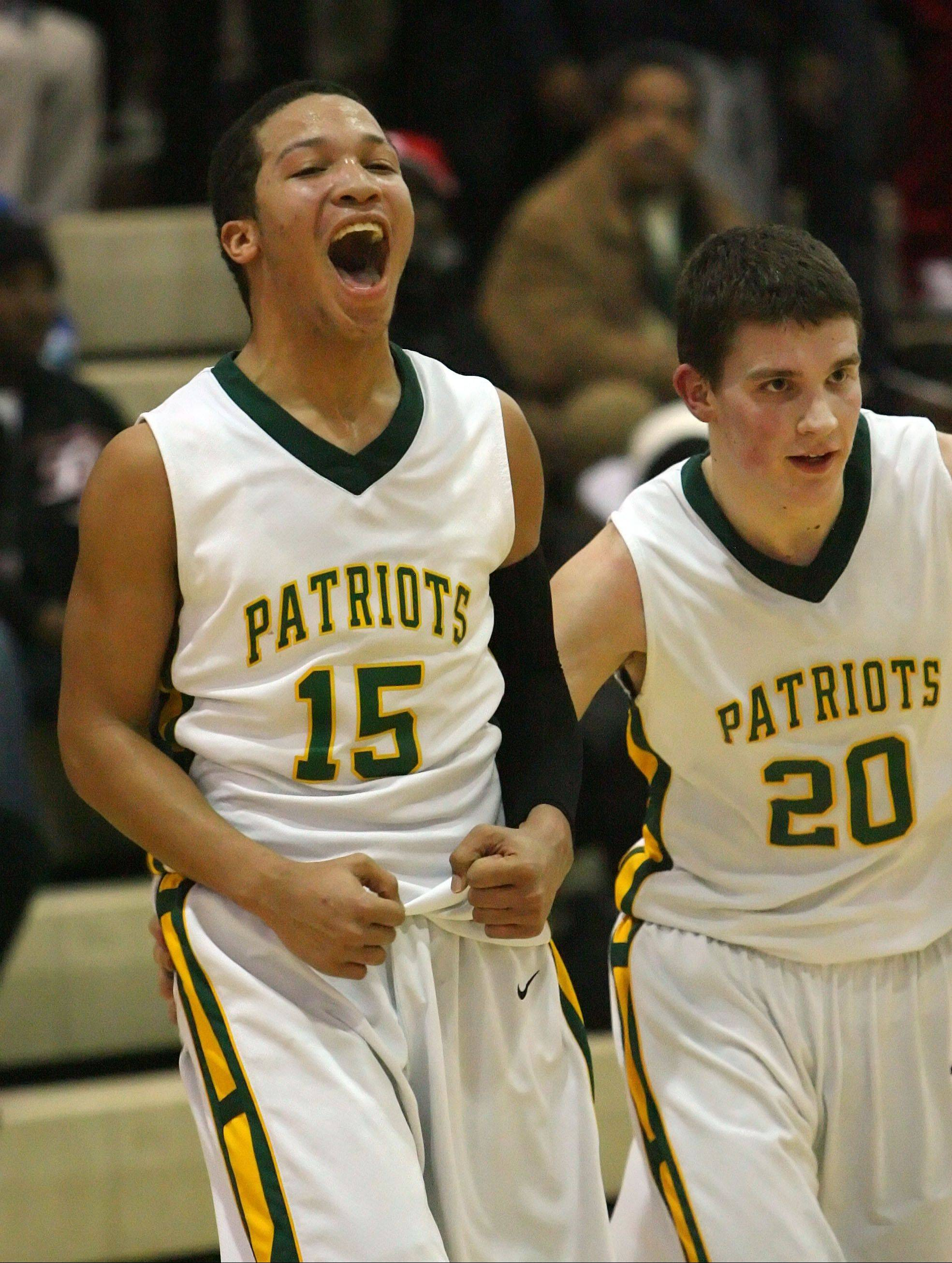 Stevenson's Jalen Brunson, left, celebrates with teammate Matthew Morrissey after the Patriots beat North Chicago in the NSC title game Wednesday night at Stevenson.