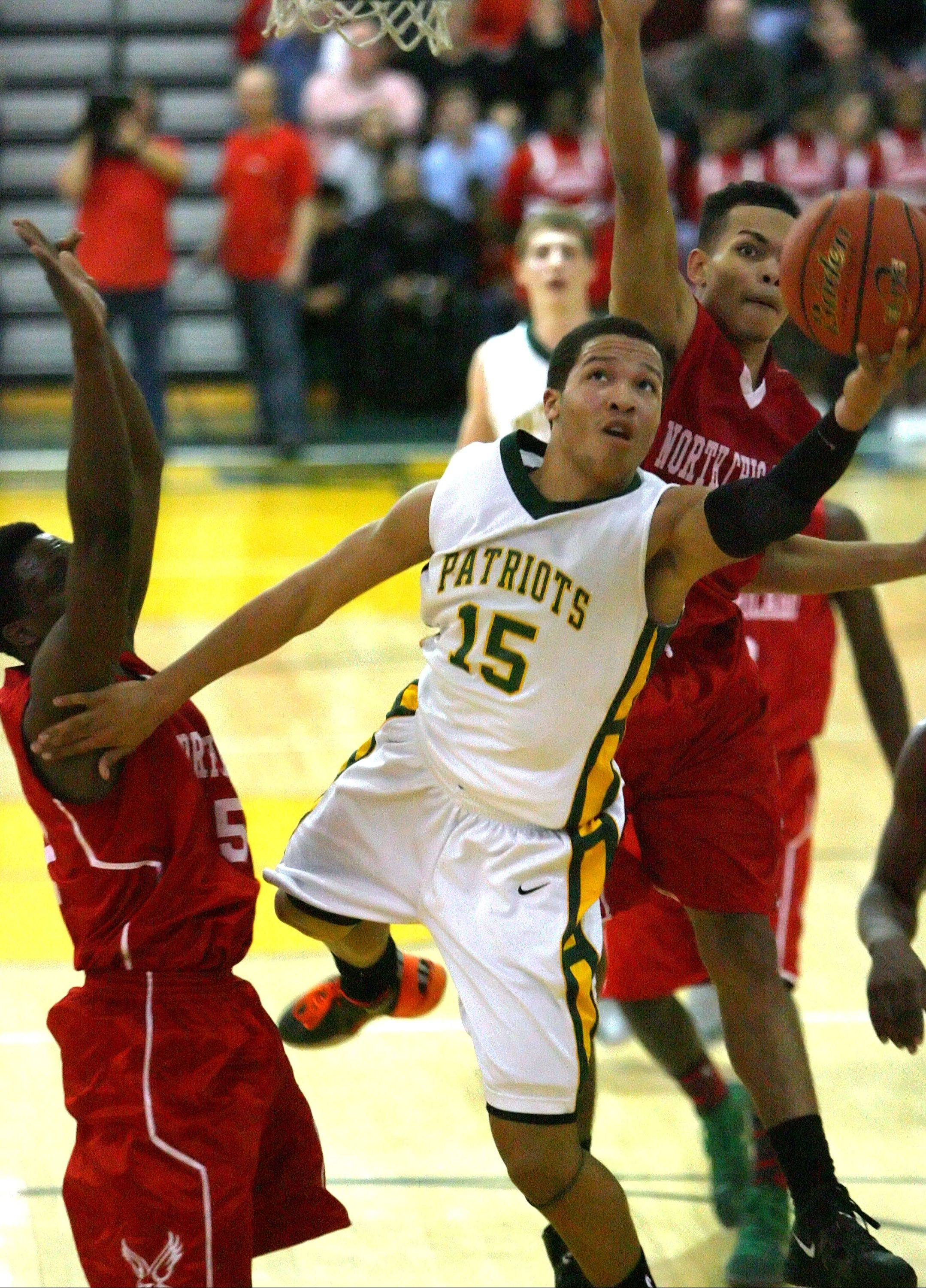 Stevenson's Jalen Brunson drives to the hoop past North Chicago's Jarrod Coleman, left, and Emmanuel January during the NSC title game Wednesday night at Stevenson.