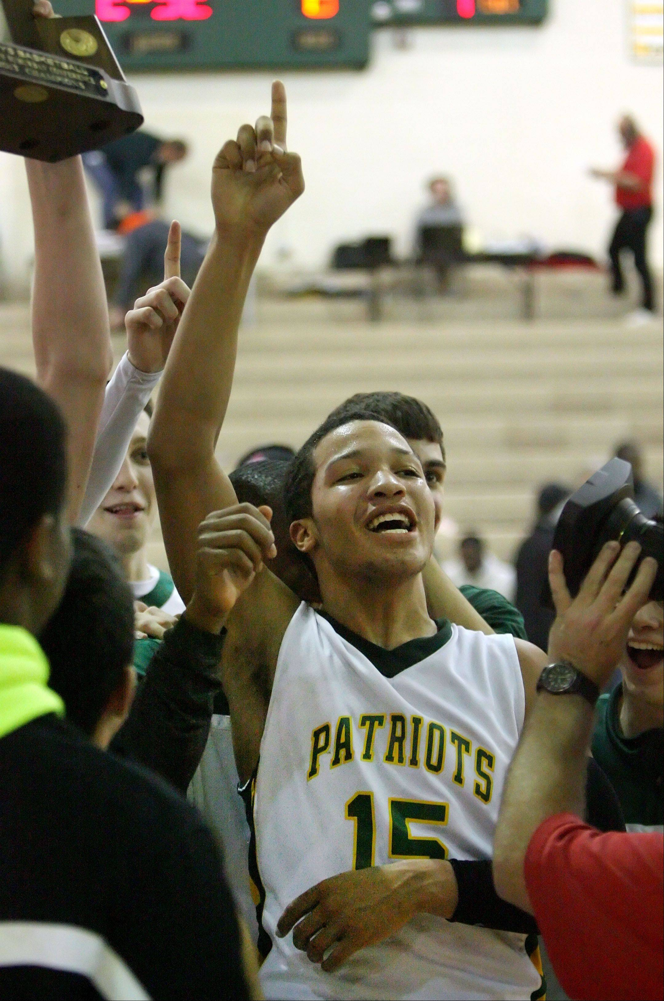Stevenson's Jalen Brunson celebrates with teammates after the Patriots beat North Chicago in the NSC title game Wednesday night at Stevenson.