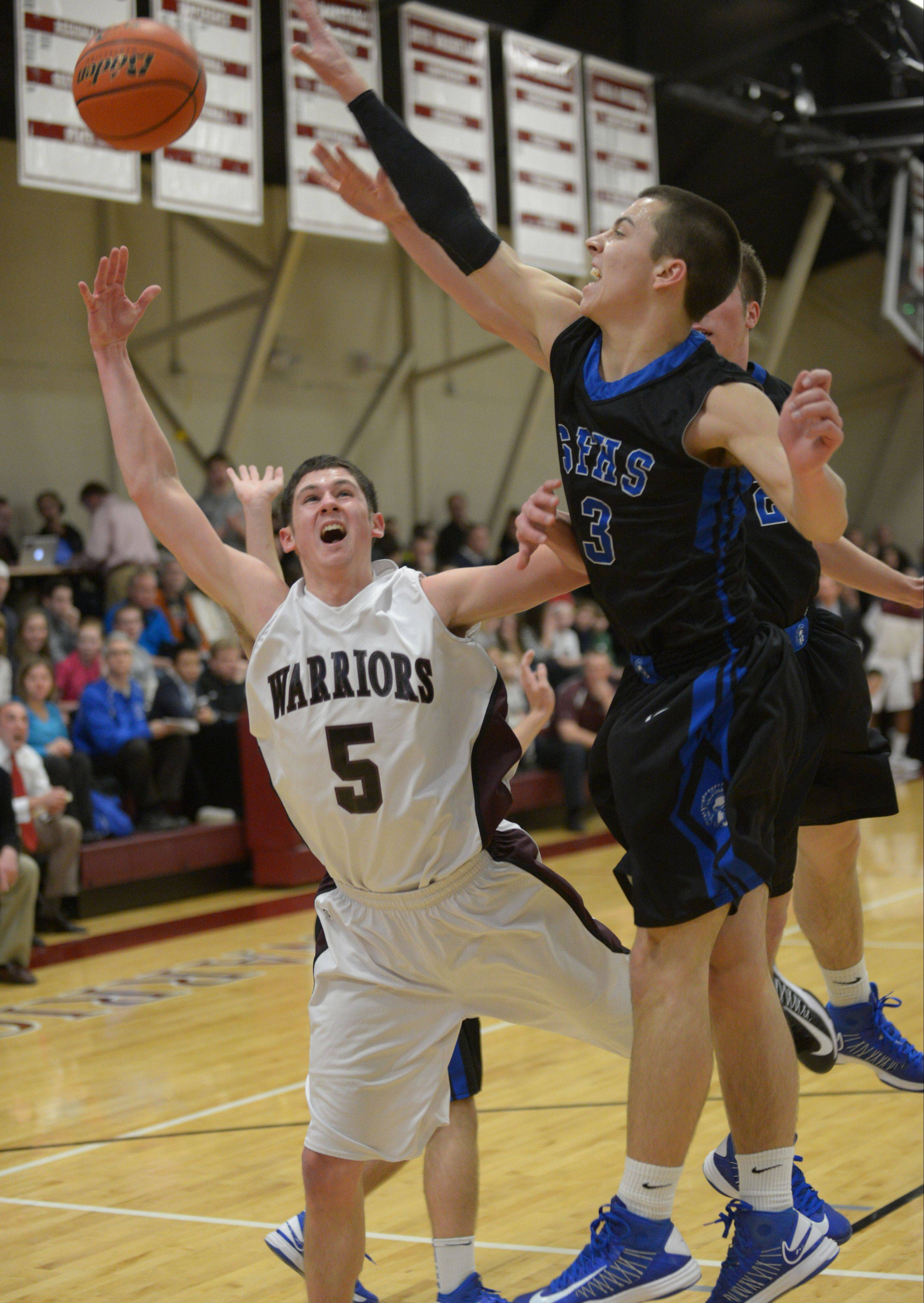Jason Pisarski of St. Francis tries to block a shot by Wheaton Academy's Collin Roy.