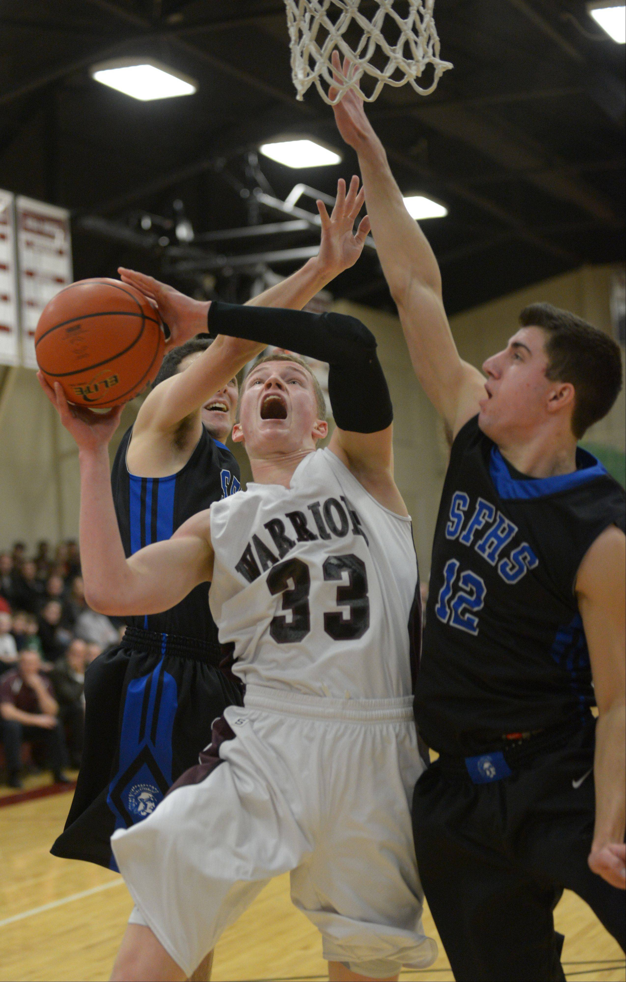 Brandon Ruggles,left, of Wheaton puts up a shot as Tim Zettinger of St. Francis attempts to block.