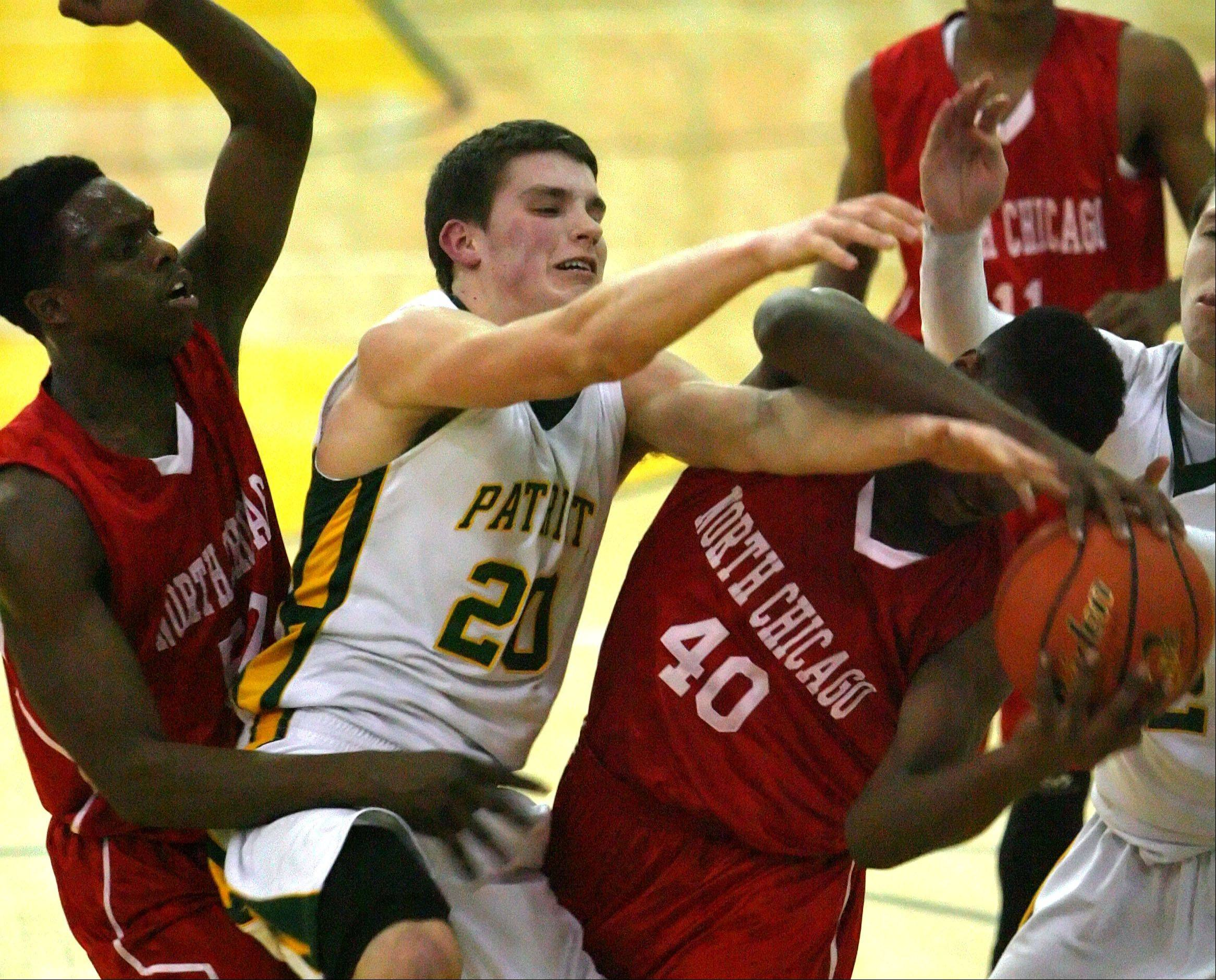 Stevenson's Matthew Morrissey, middle, battles for a rebound with North Chicago's Jarrod Coleman, left, and Joseph Thomas .