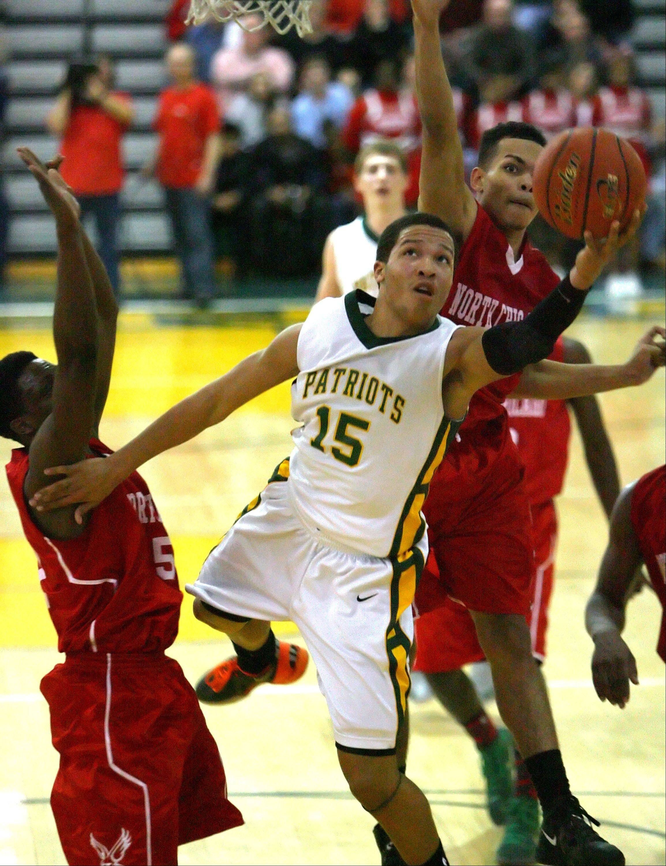 Stevenson's Jalen Brunson drives to the hoop past North Chicago's Jarrod Coleman, left, and Emmanuel January.