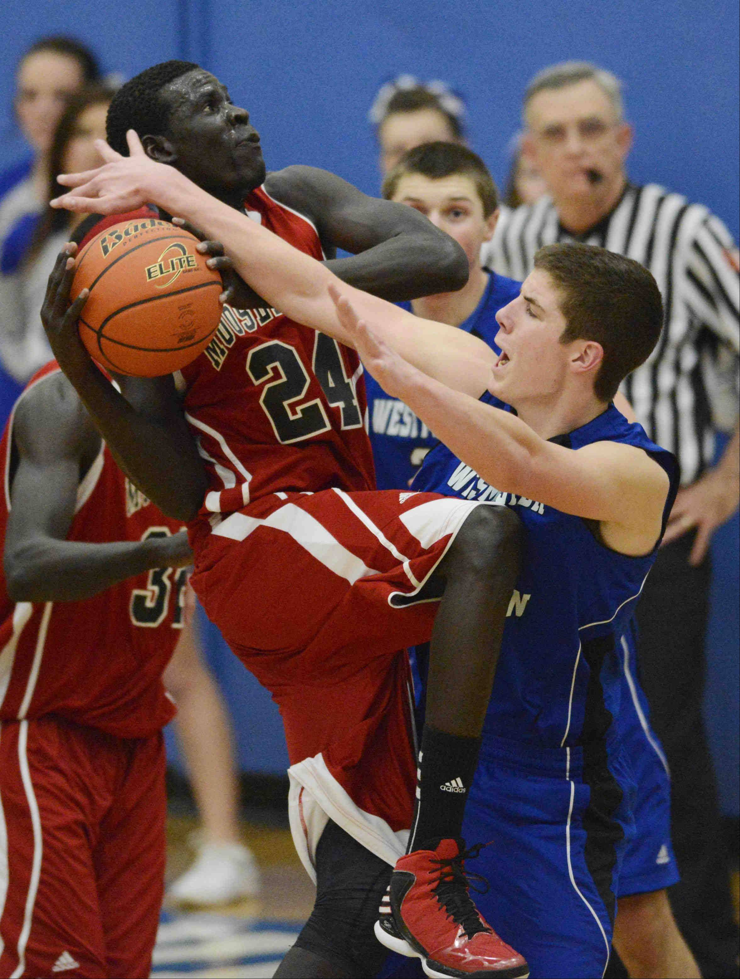 Westminster Christian's Sam Carini holds steady as Mooseheart's Mangisto Deng drives. Traveling was called against Deng.