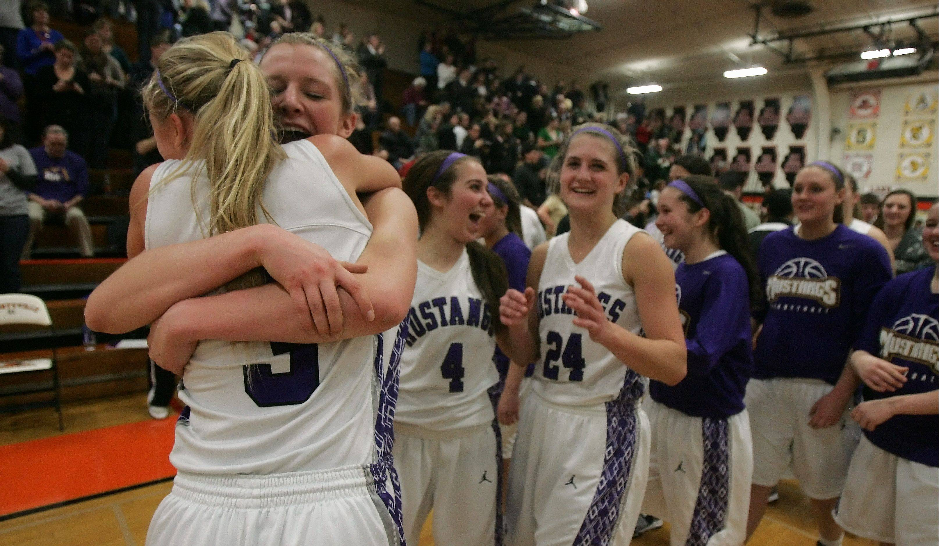 Rolling Meadows' Jackie Kemph, left, hugs teammate Jenny Vliet after the Mustangs topped Fremd in the Class 4A Libertyville sectional final Thursday.