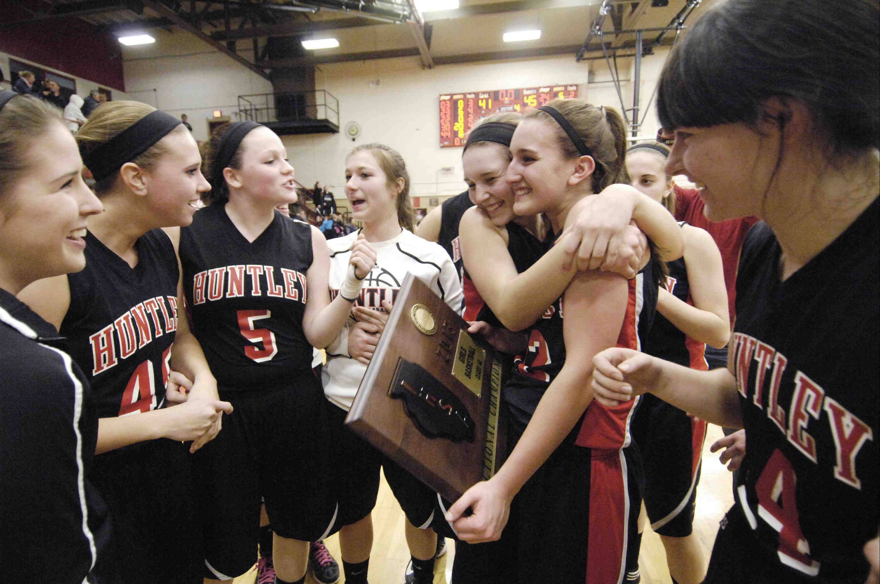 Huntley's Sam Andrews hugs teammate Haley Ream, who holds the Class 4A sectional championship plaque after the Red Raiders defeated Streamwood Thursday in Rockford.
