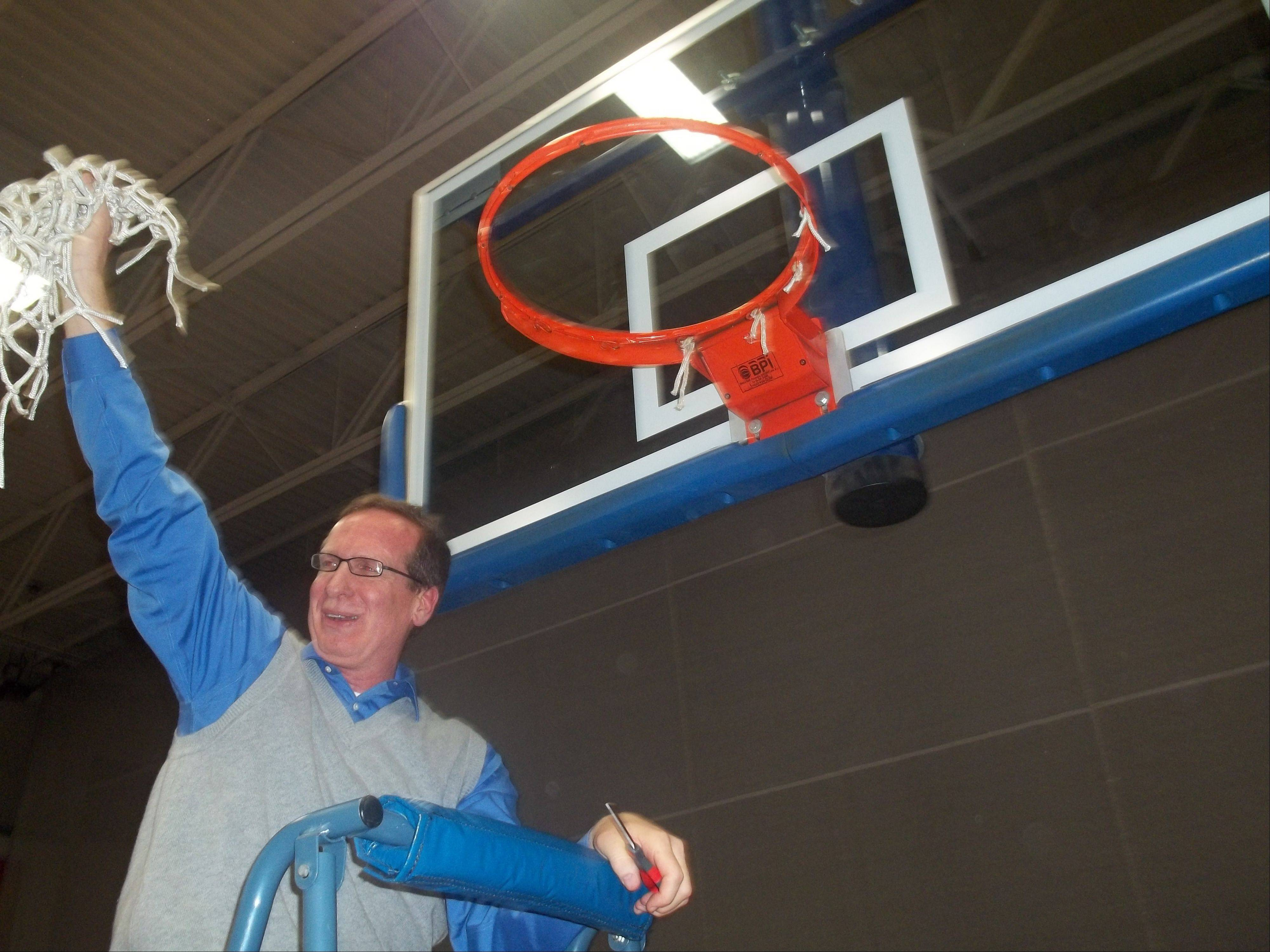 Burlington Central girls basketball coach Mark Smith shows the net to the Rockets' fans after their 49-26 win over Sterling in the Class 3A Genoa-Kingston sectional championship game Thursday.