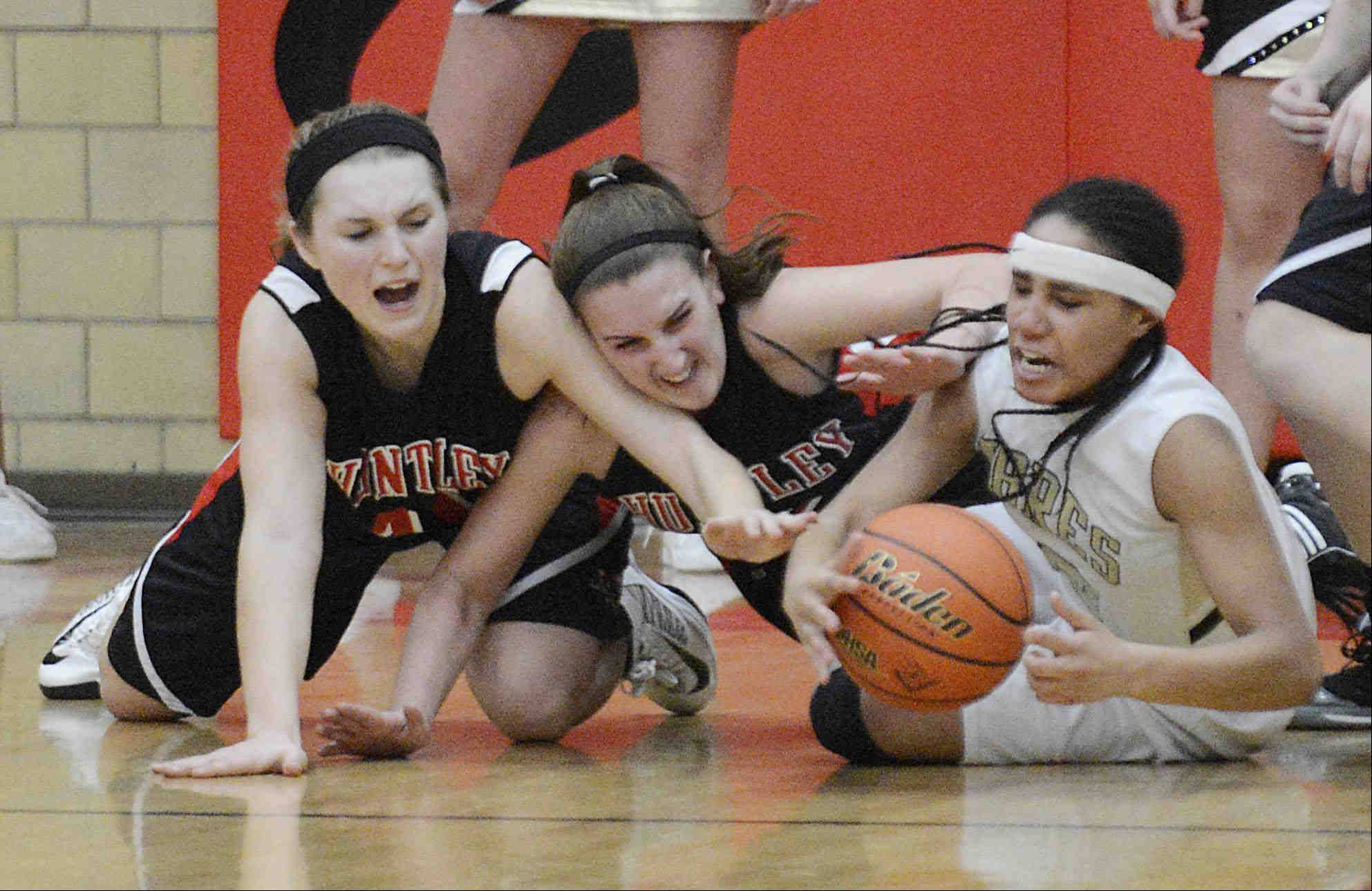 Huntley's Sam Andrews, left, and Haley Ream pressure Streamwood's Deja Moore in the closing seconds of the game.