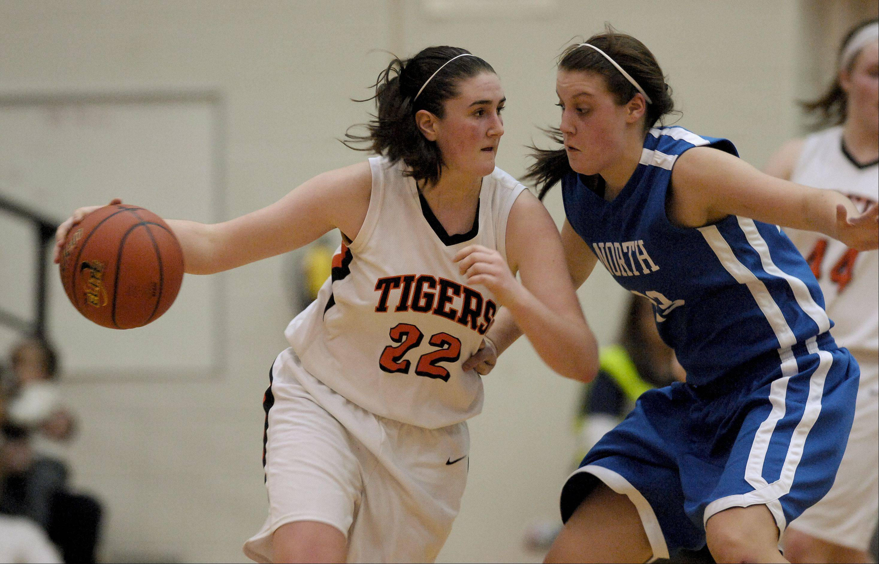 Melinda Franke of Wheaton Warrenville South looks to drive around Chrissy Baird of Wheaton North .
