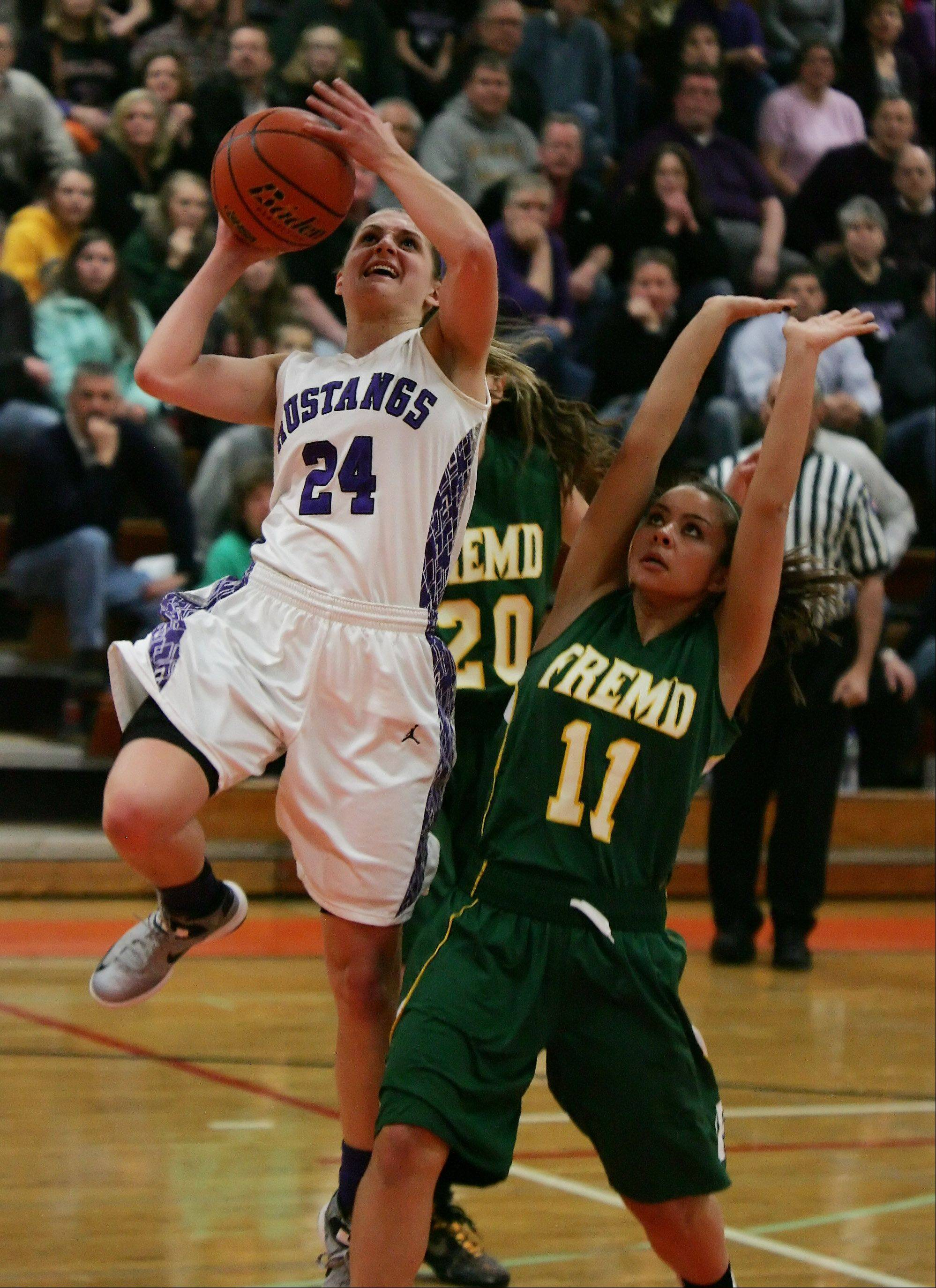 Rolling Meadows guard Alexis Glasgow drives past Fremd guard Catherine Ernst.