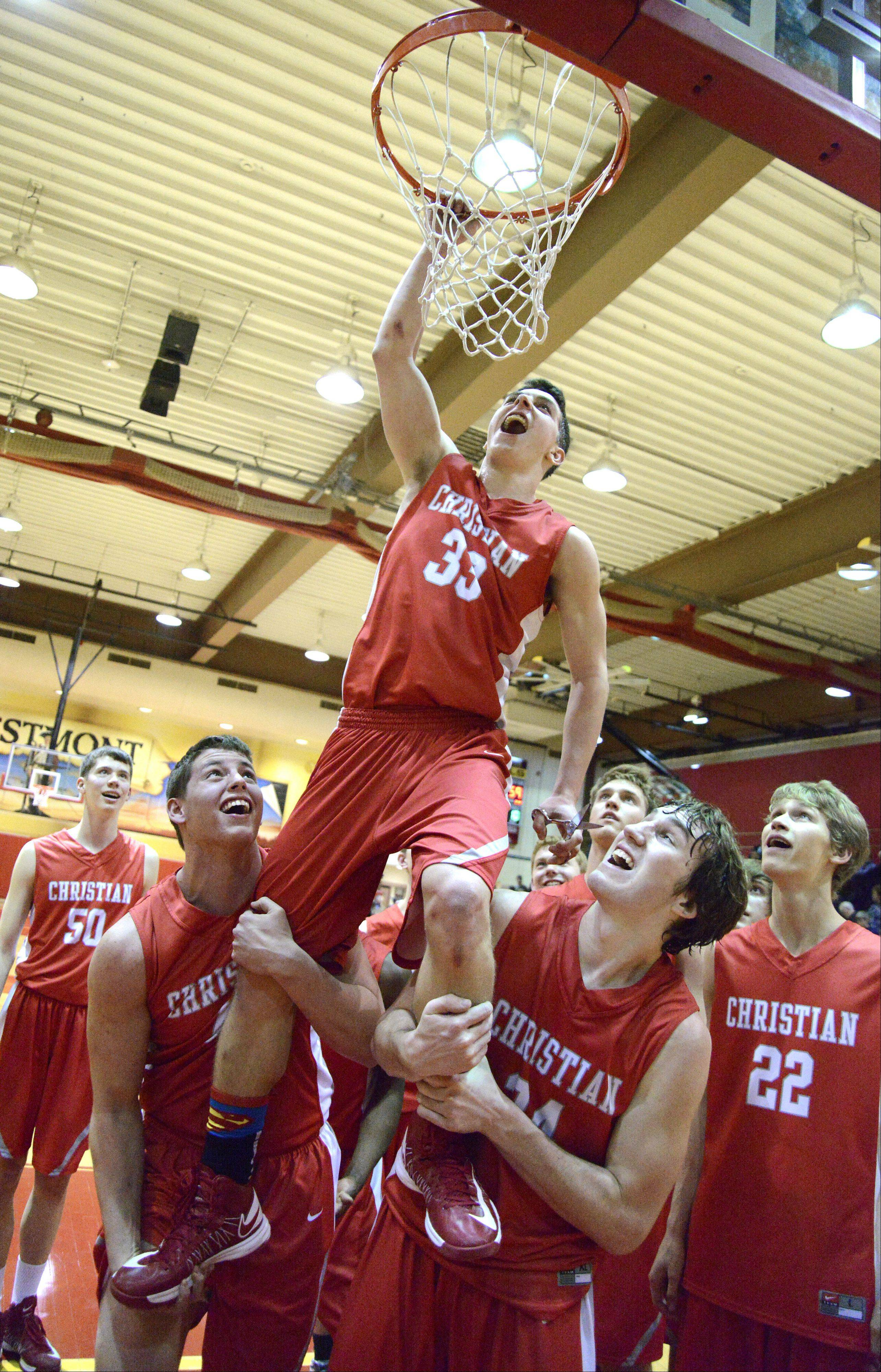 Aurora Christian's Ryan Suttle is hoisted by teammates Jake Gelbato, left, and Cory Windle to be the first to cut the hoop. Suttle sunk the game winning shot.