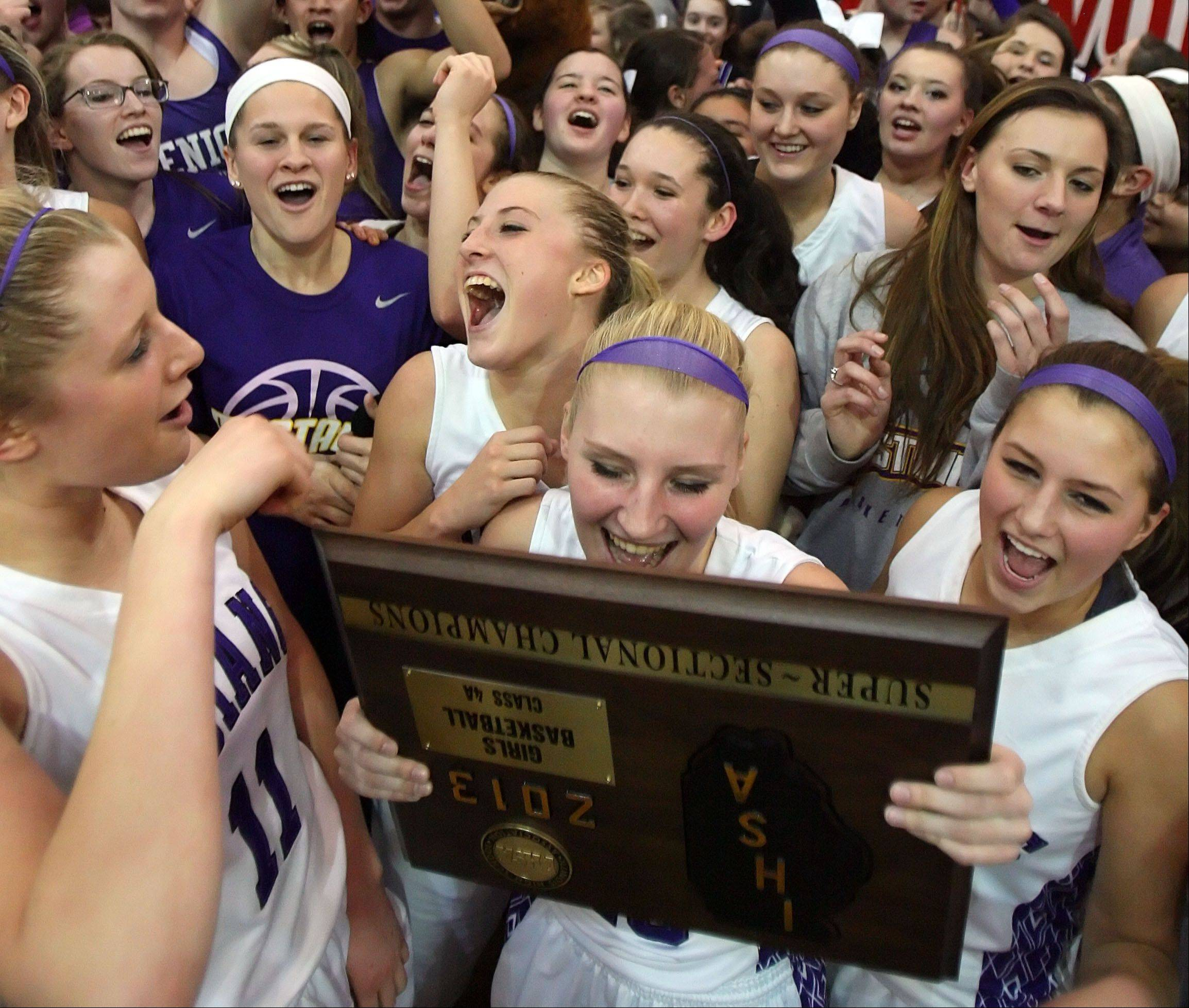 Rolling Meadows' players celebrate with the supersectional trophy after beating Evanston in Class 4A Niles West supersectional play Monday night in Skokie.