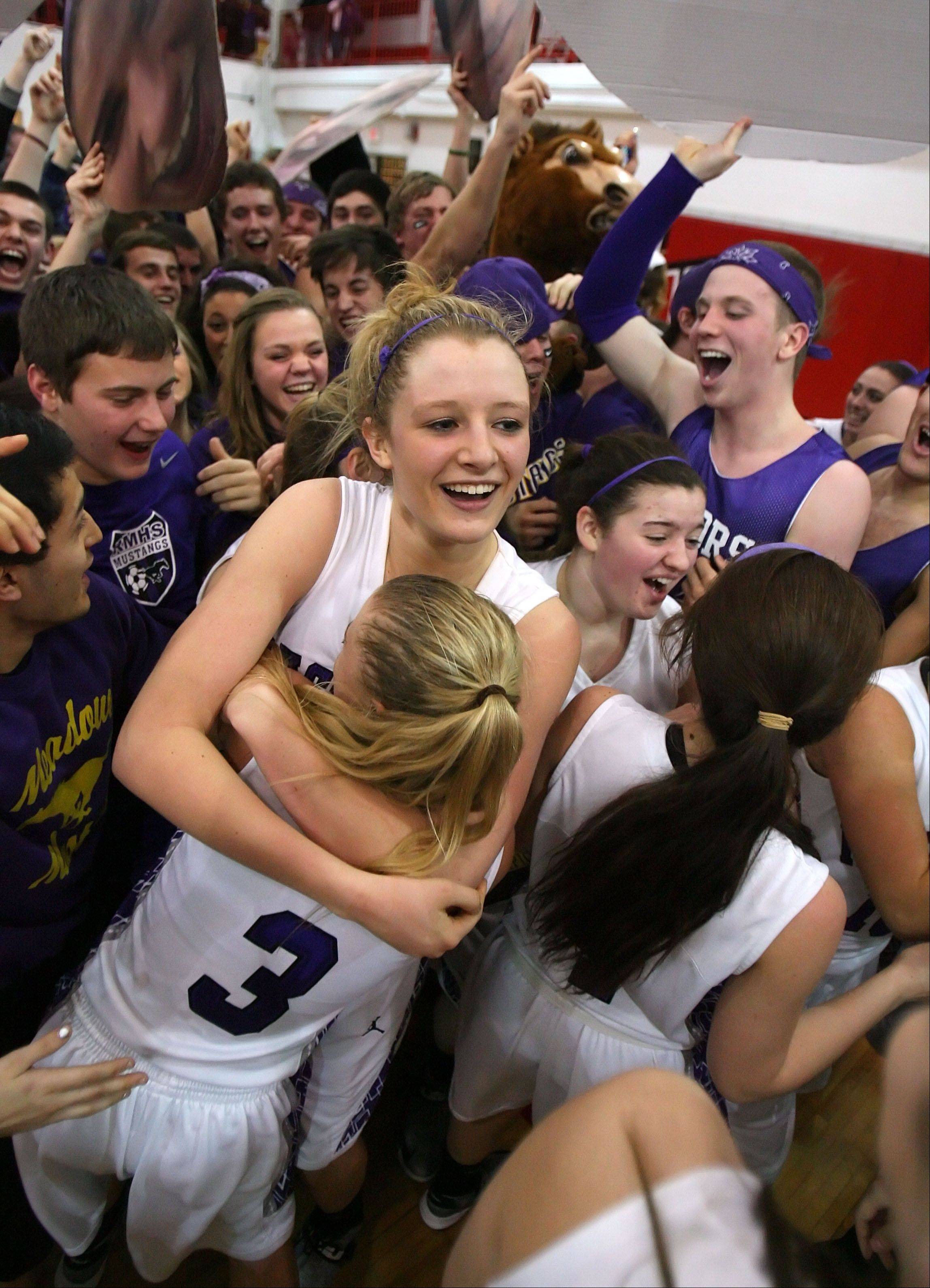 Rolling Meadows' Jenny Vliet is hoisted above the fray by teammate Jackie Kemph as the fans rush the floor after the Mustangs topped Evanston in Class 4A Niles West supersectional play Monday night in Skokie.