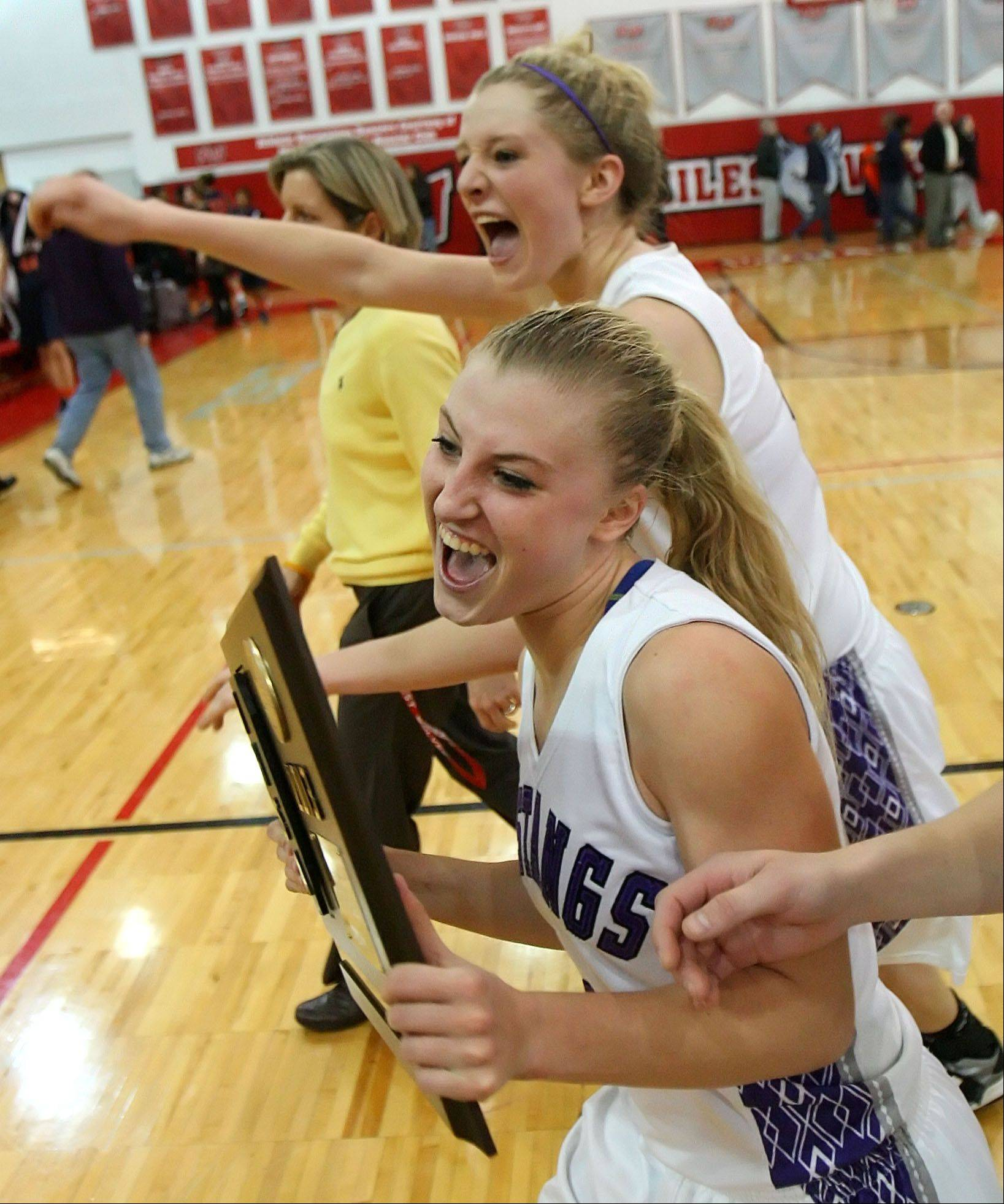 Rolling Meadows' Jenny Vliet, back, and Jackie Kemph bring the trophy back to their team after beating Evanston in Class 4A Niles West supersectional play Monday night in Skokie.