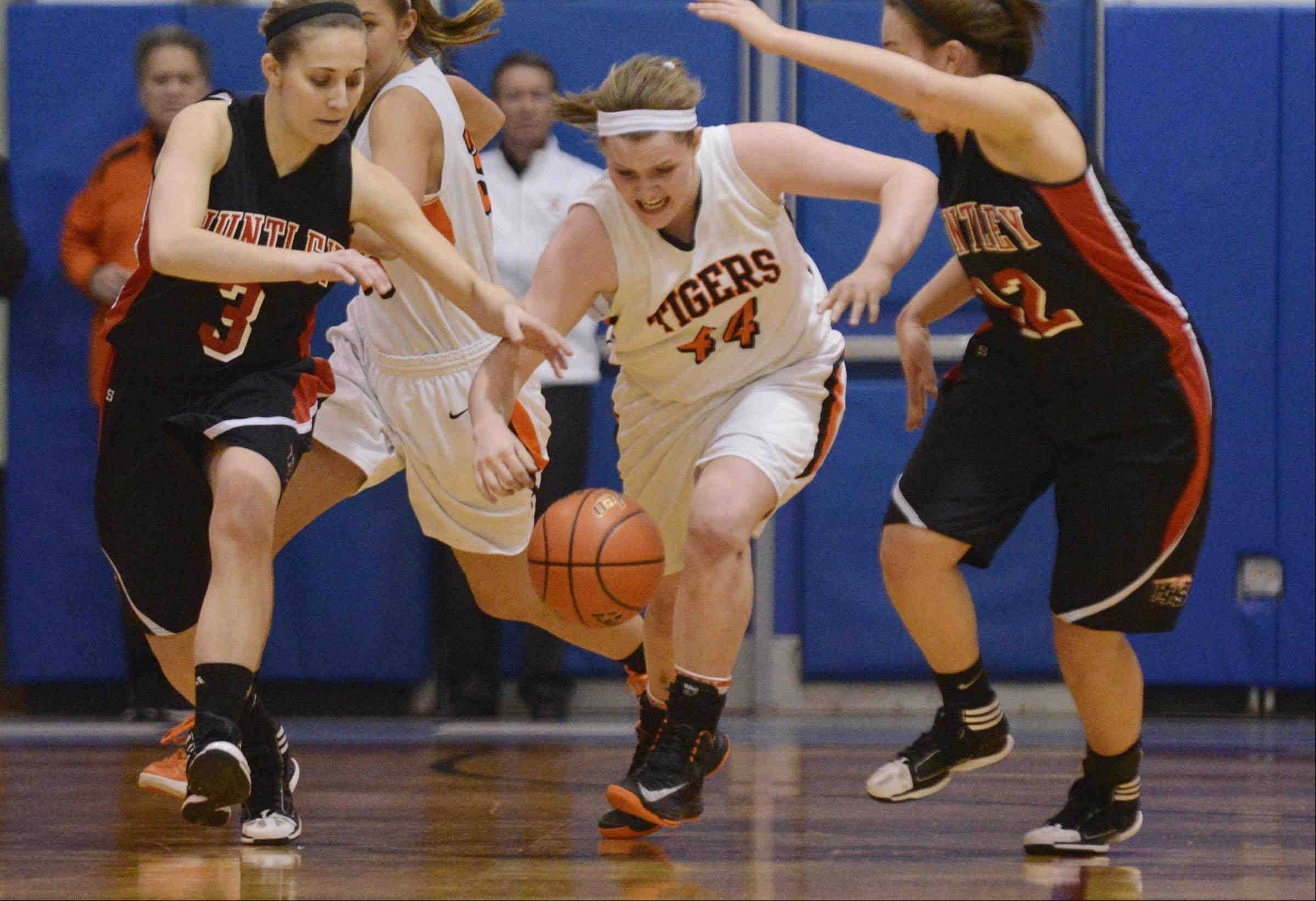Wheaton Warrenville South's Olivia Linebarger chases a loose ball with Huntley's Amanda Kaniewski and Haley Ream Monday in the Class 4A Dundee-Crown supersectional game in Carpentersville.