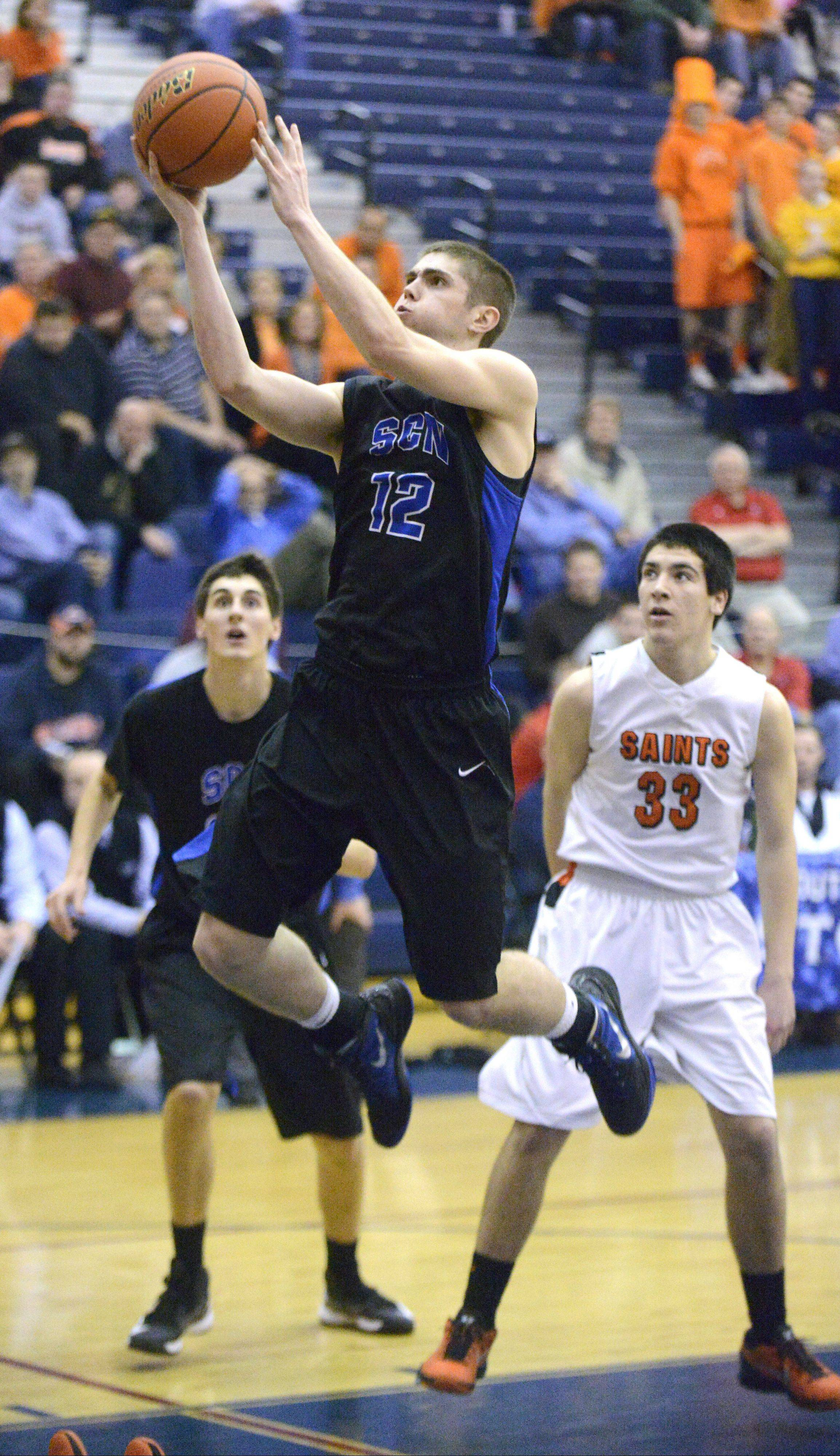 St. Charles North's Quinten Payne soars to the hoop past St. Charles East's Jake Asquini in the fourth quarter of the Class 4A South Elgin regional on Wednesday. Payne led all scorers with 26 points.